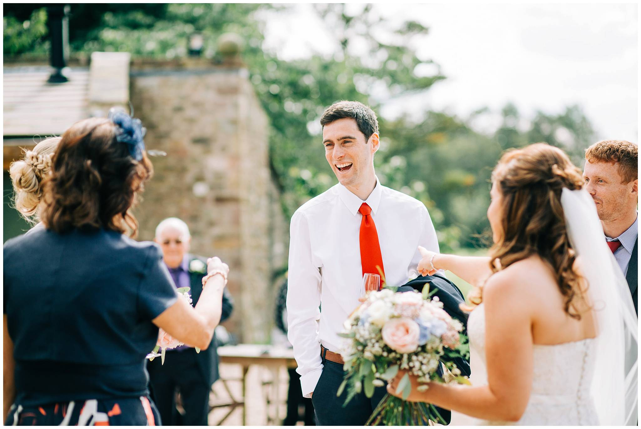 man in bright red tie is smiling and laughing with other wedding guests outside