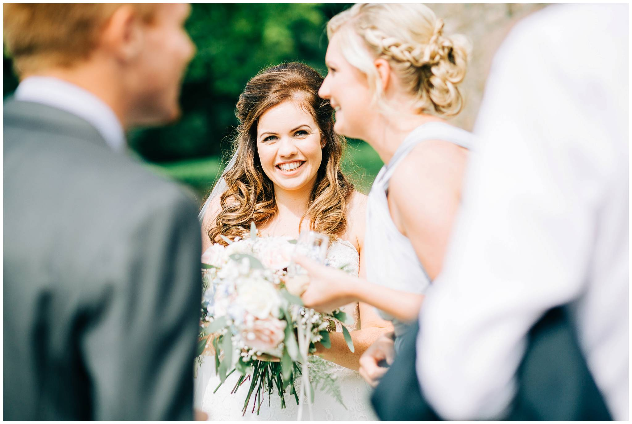 bride smiling and looking at bridesmaid in conversation with another guest