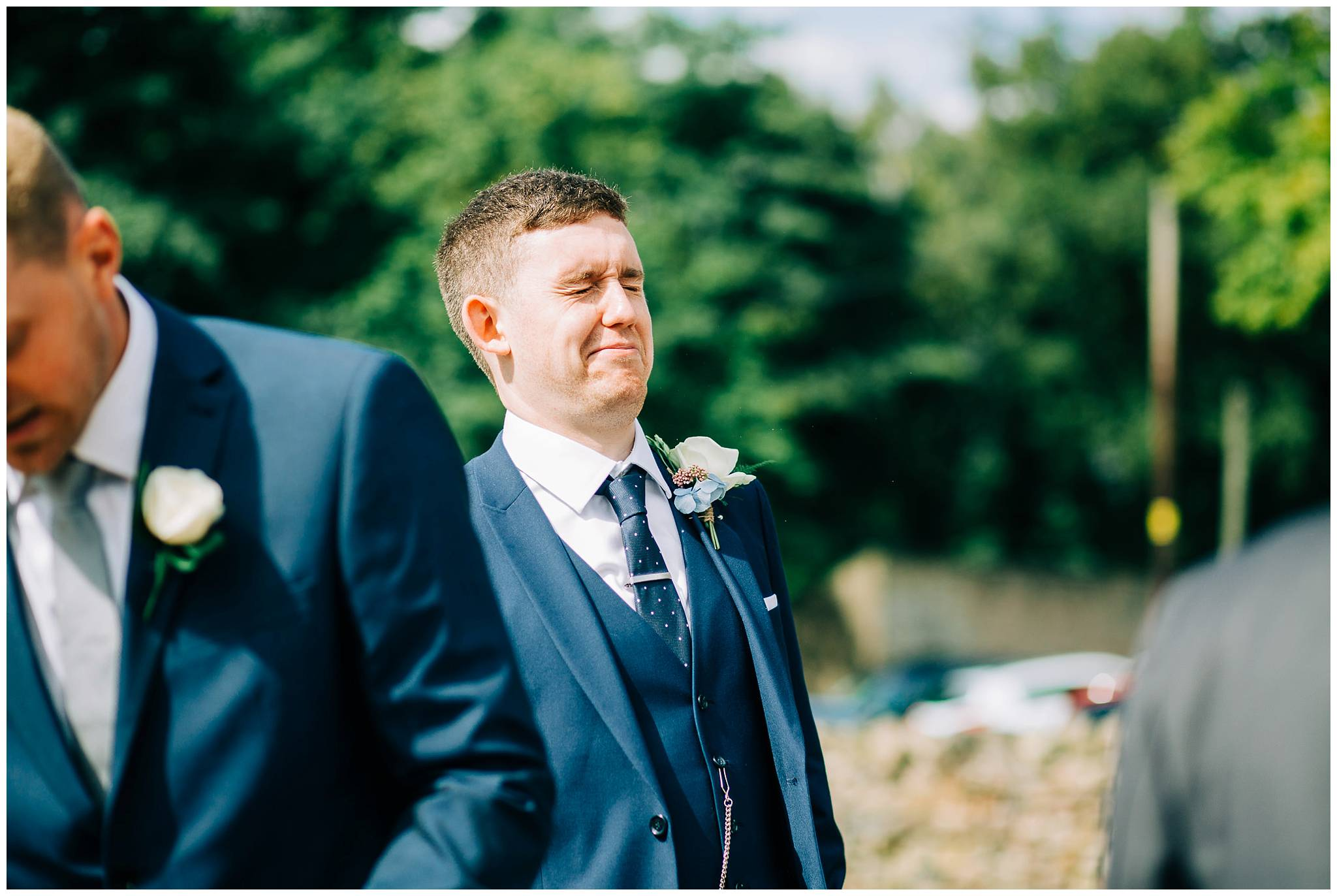 groom pulling funny face with closed eyes laughing at wedding guest