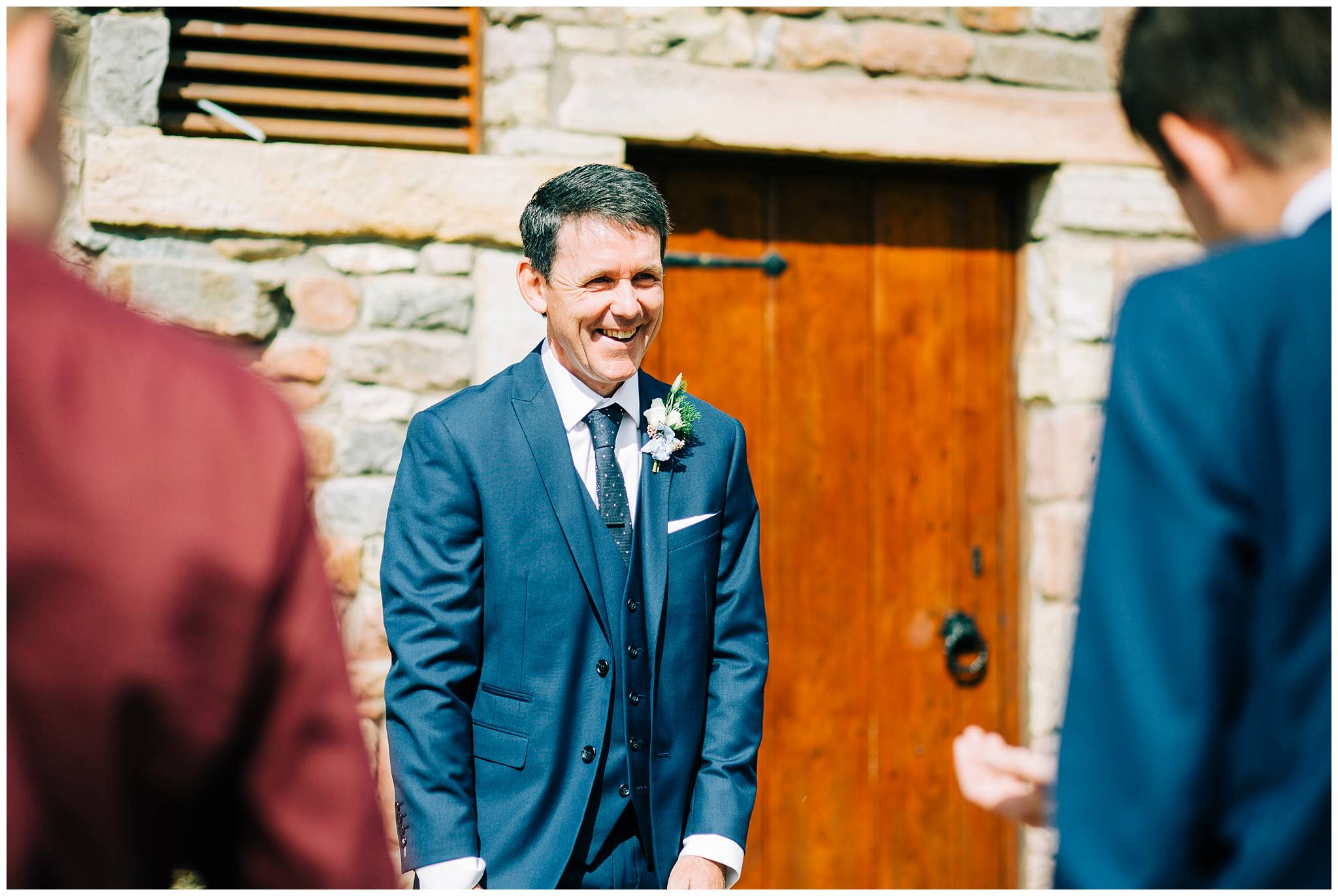 father of groom laughing and smiling outside rustic walls of browsholme hall and tithe barn