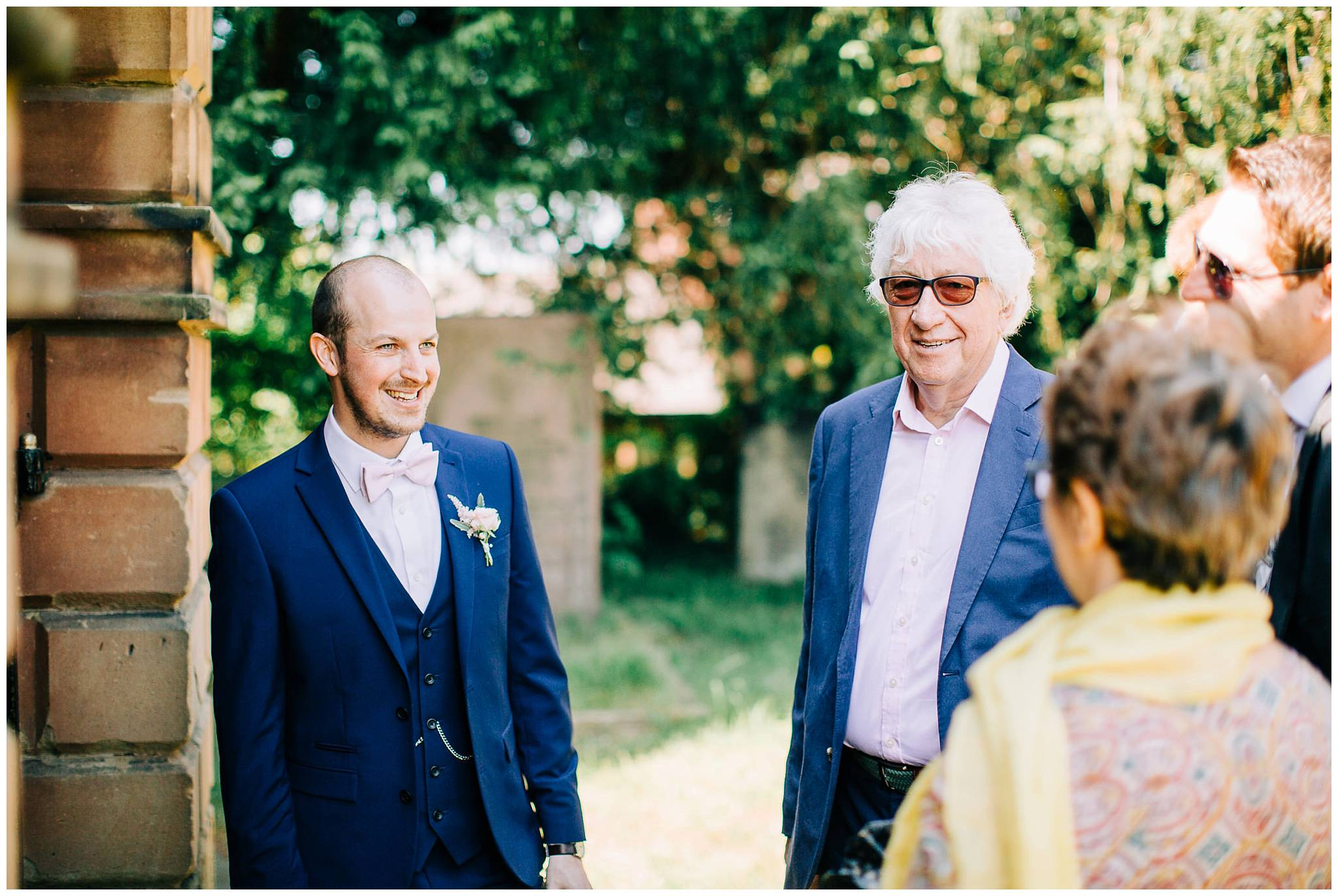 Groom smiling whilst chatting to arriving guests