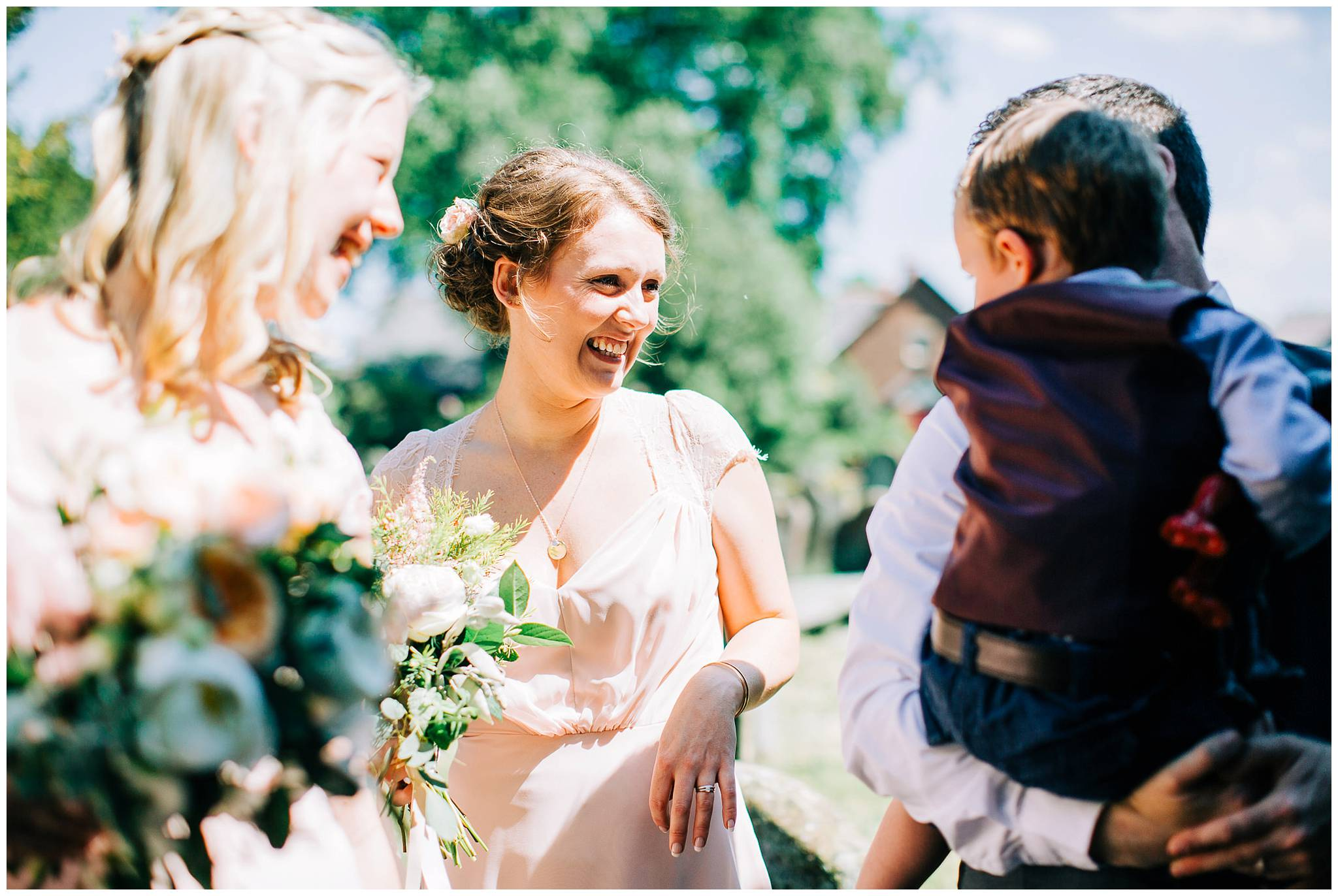 another bridesmaid looking at her child smiling