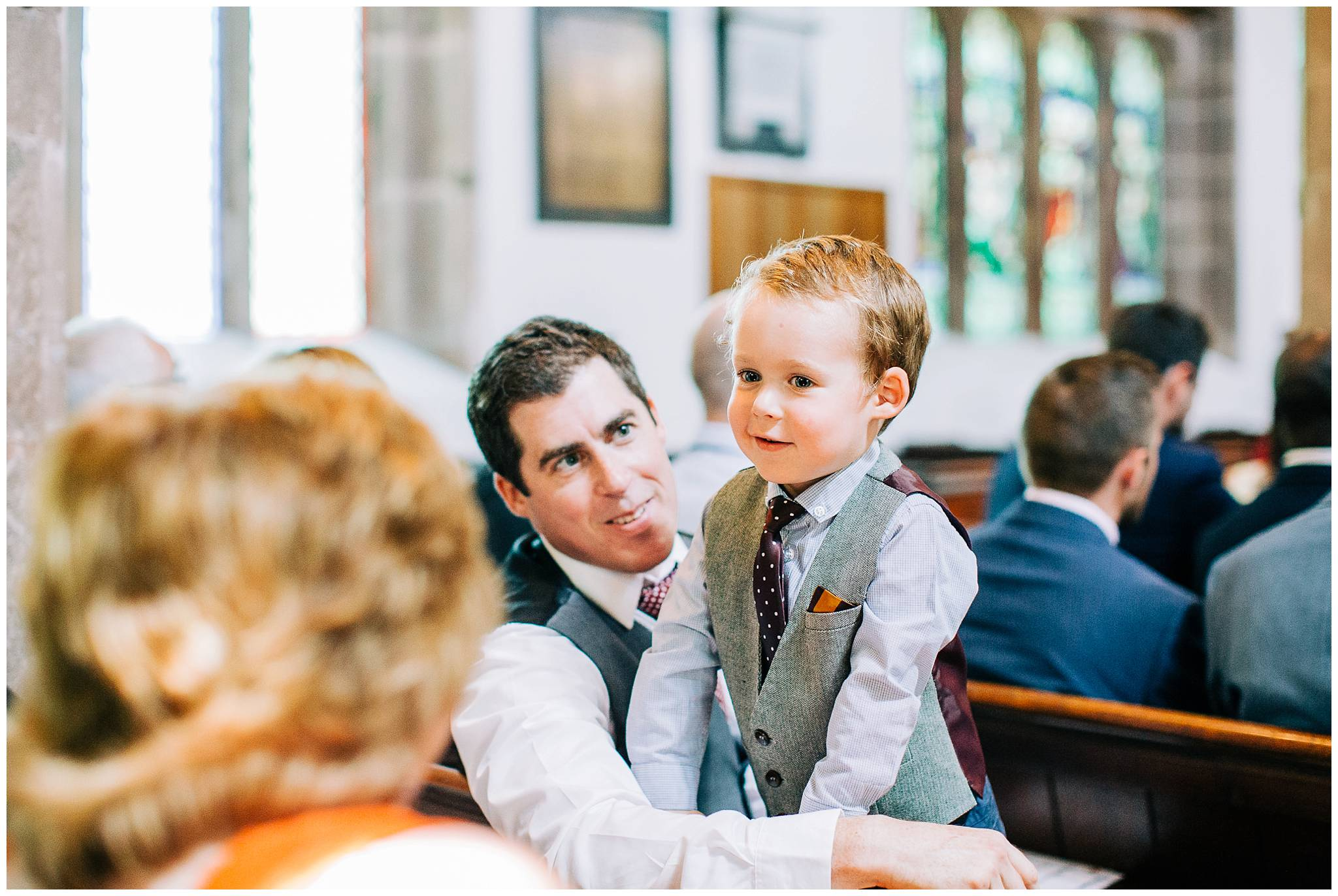 a young guest with his father sat in the church waiting for the brides entrance