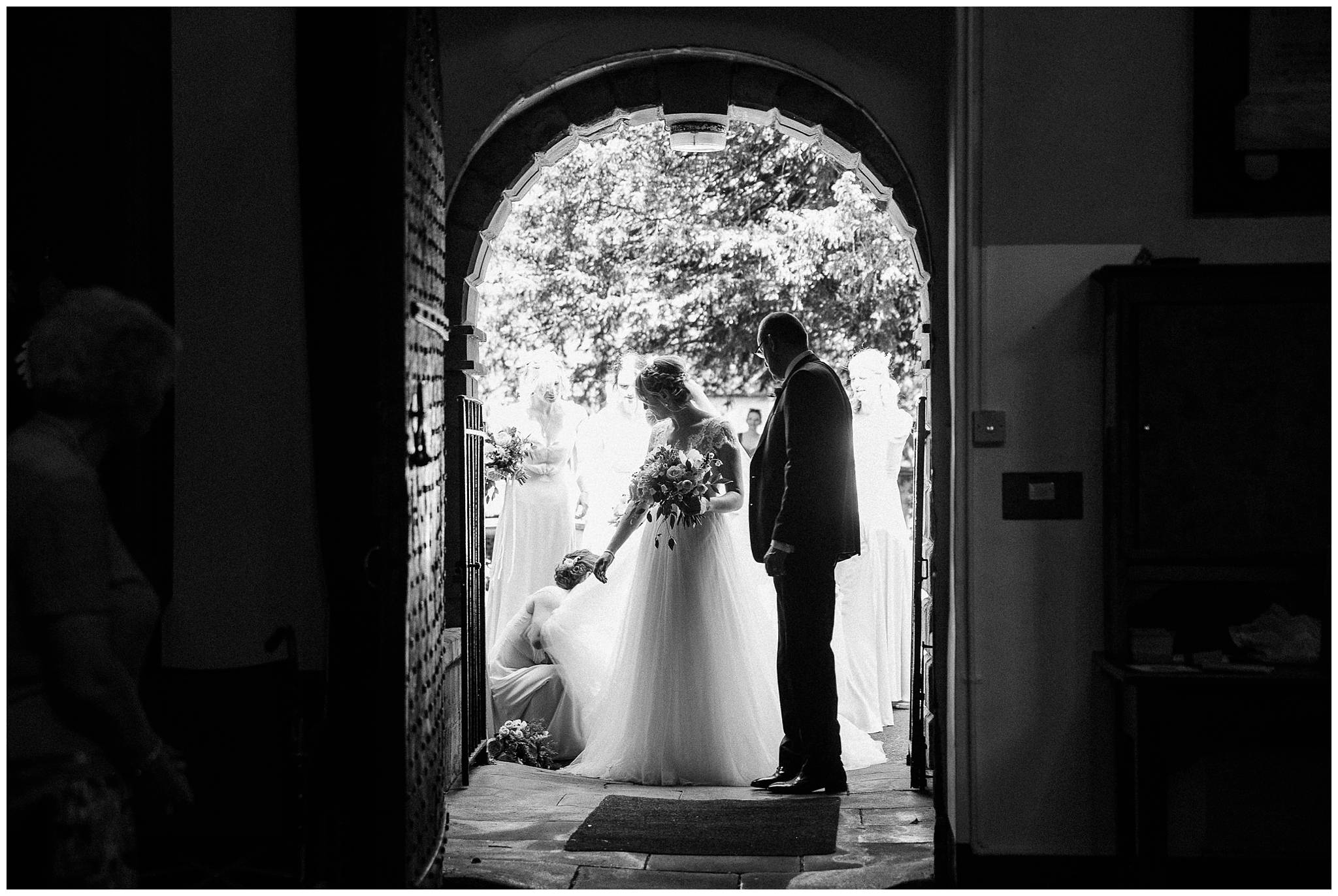 a black and white silhouette of the bride in the church entrance while her bridesmaids arrange the back of her dress