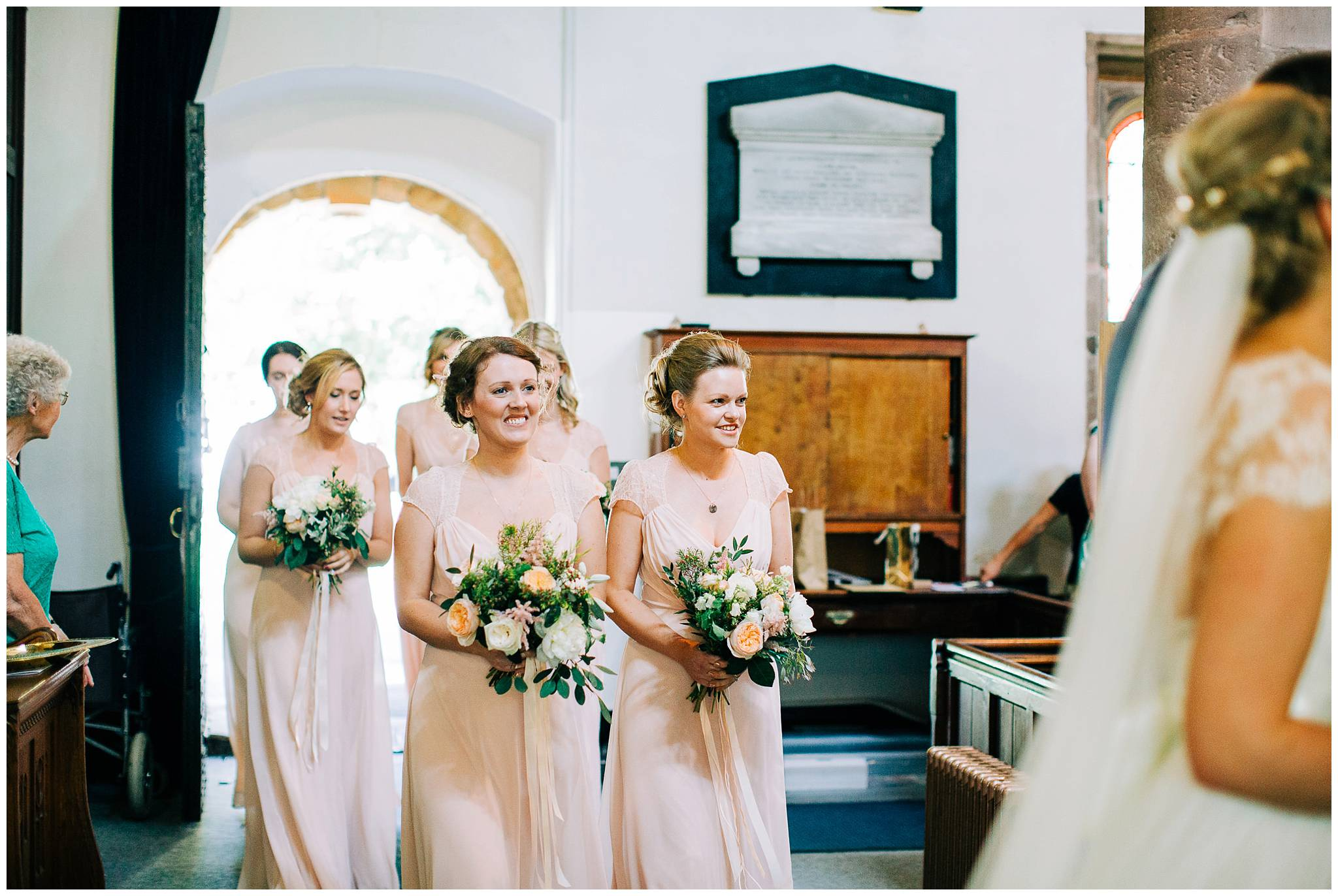 the bridesmaids wearing pale pink dresses follow the bride into the church and down the aisle