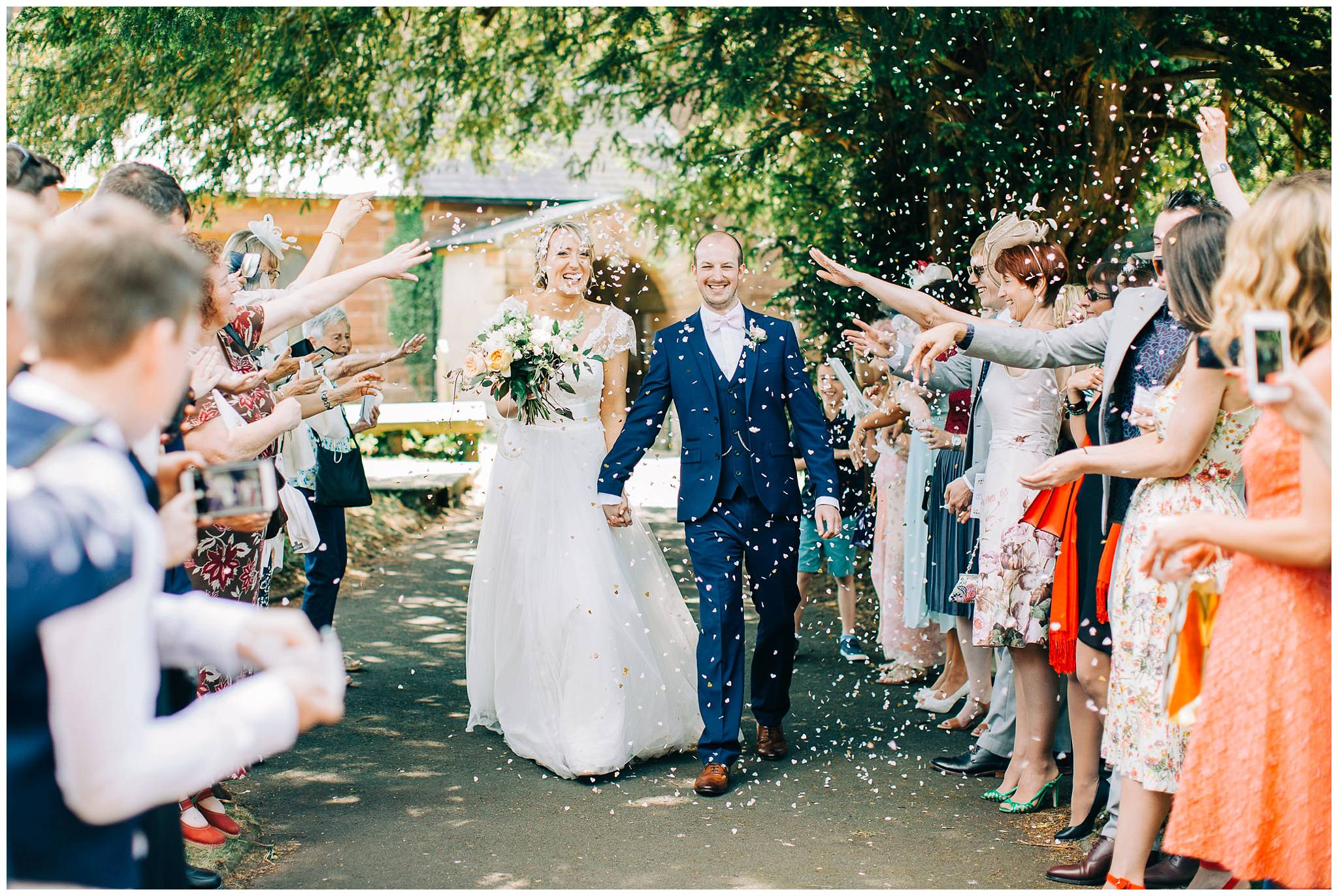 bride and groom walking hand in hand while guests throw white confetti at them