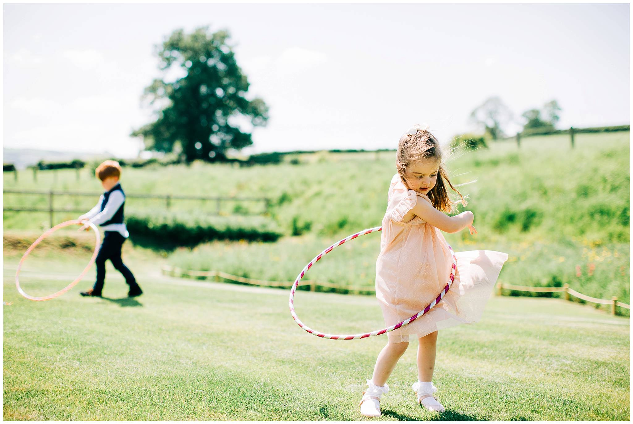 two young children playing with hula hoops on the grass at tower hill barns