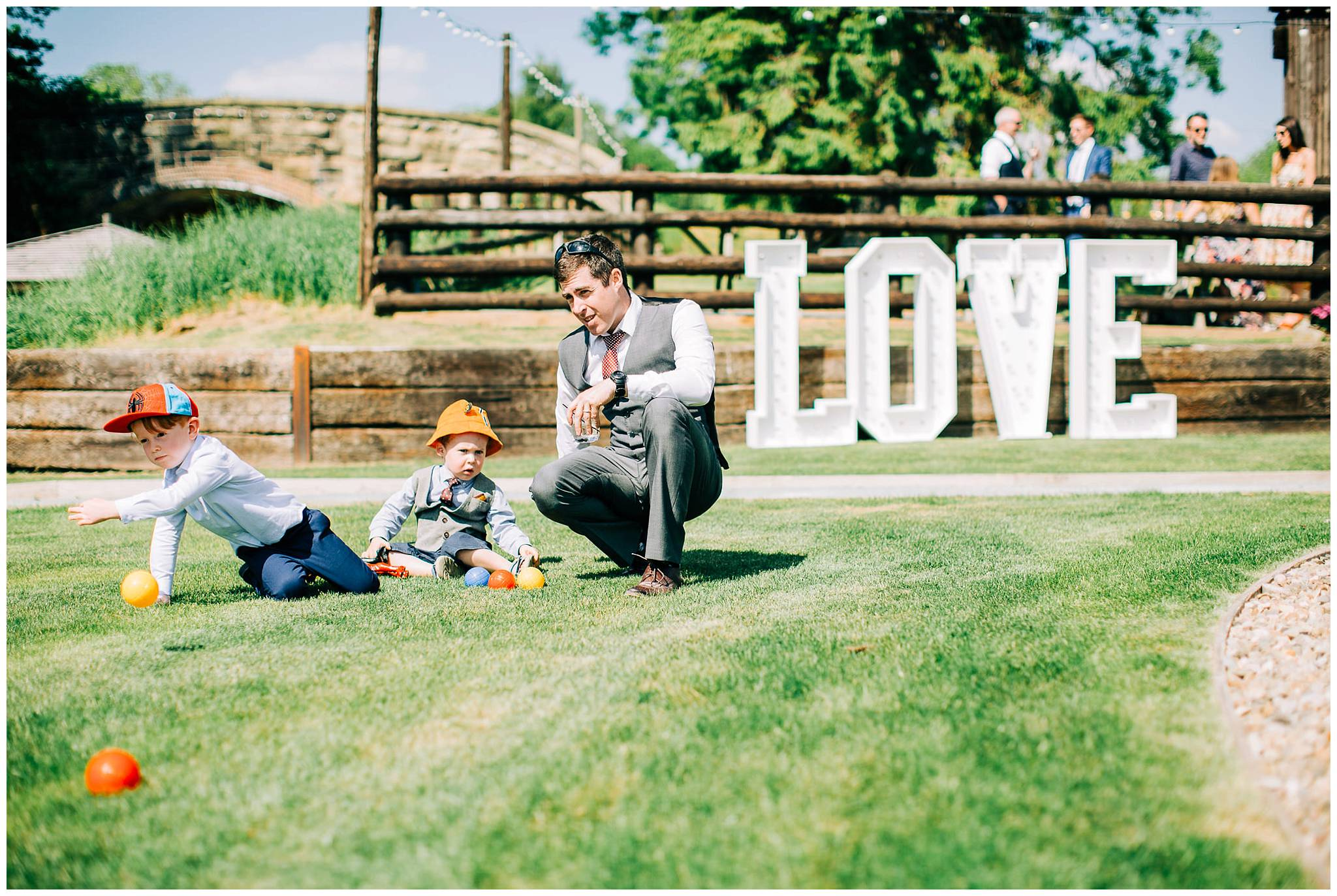 two young children with colourful sun hats are sat on the grass playing with their father
