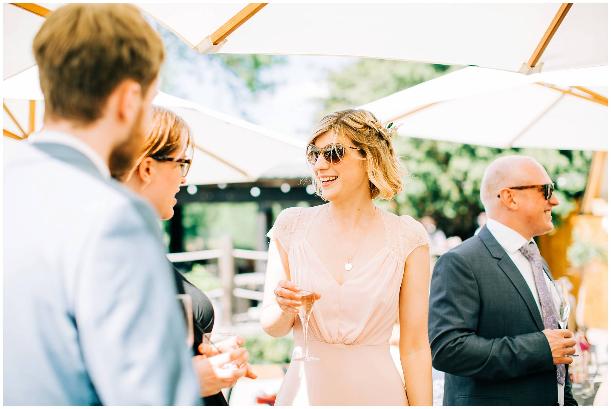 bridesmaid in light pink dress wearing sunglasses is talking to other guests