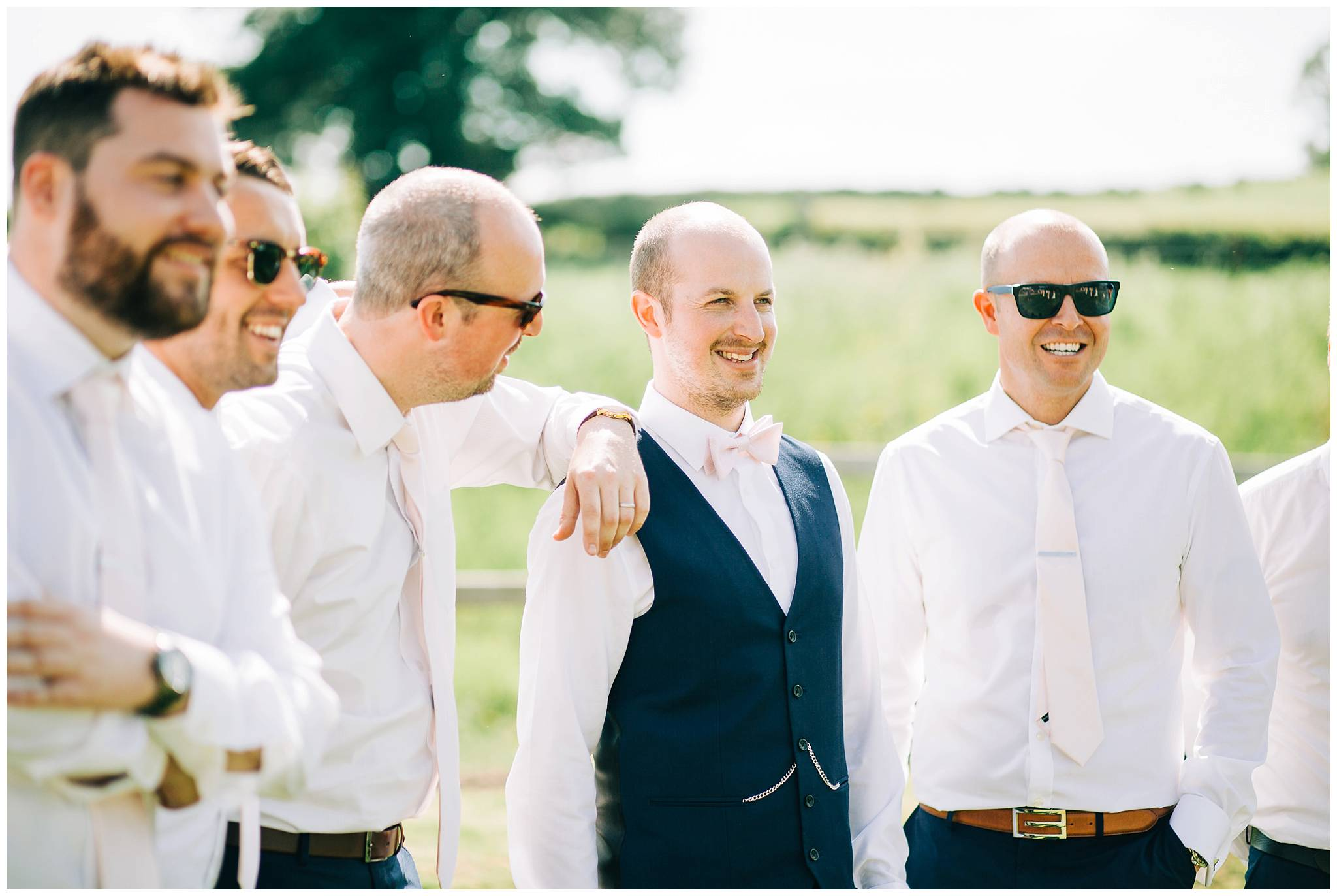 groom with all his groomsmen stood laughing and smiling for a group photograph