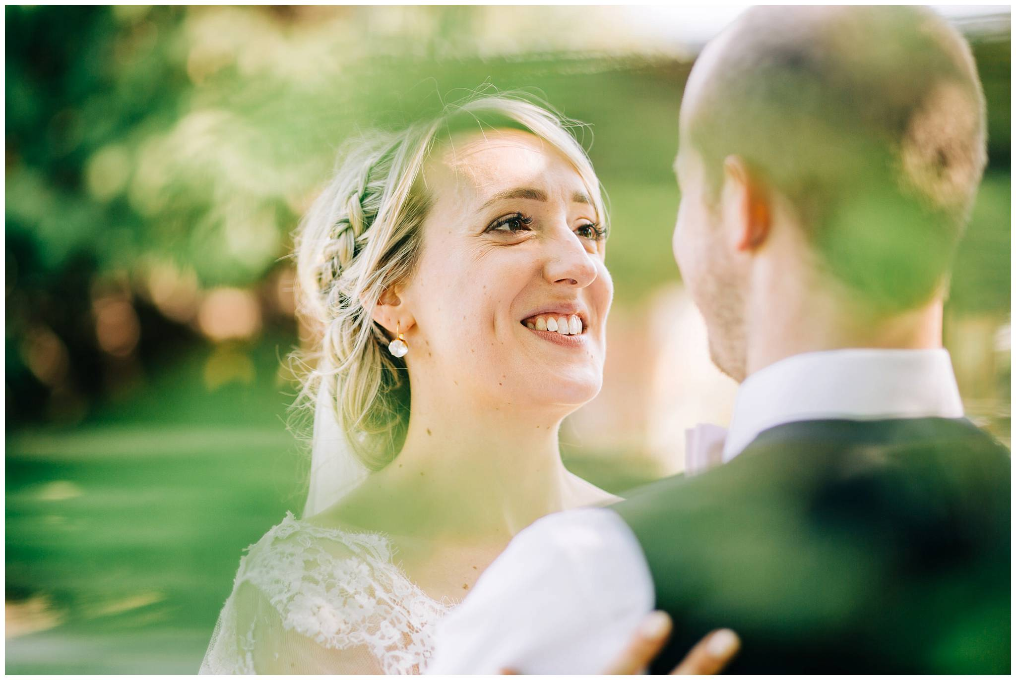 bride looking lovingly at the groom whilst stood under a tree at tower hill barns