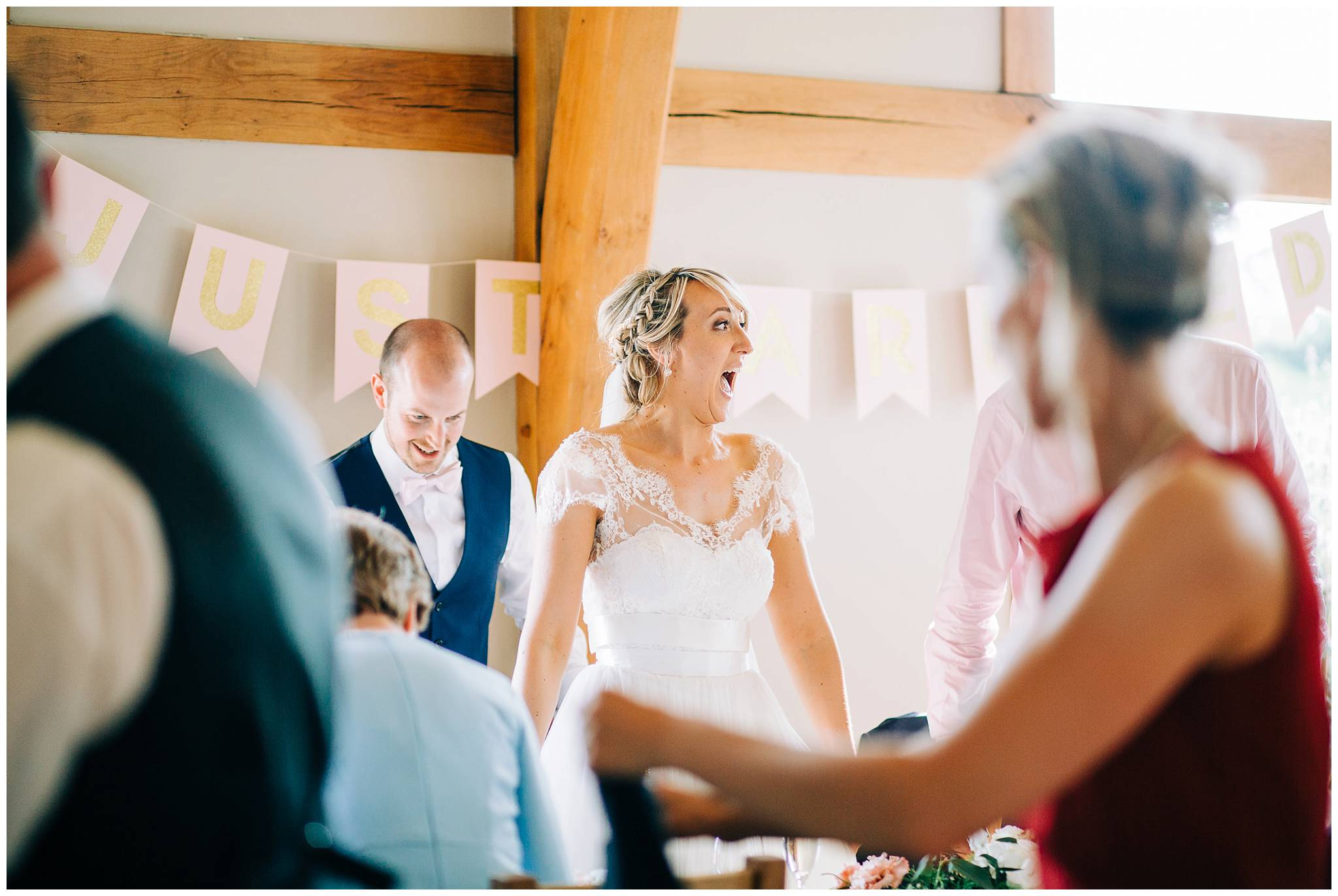 bride is smiling at everyone at the wedding breakfast before she sits down