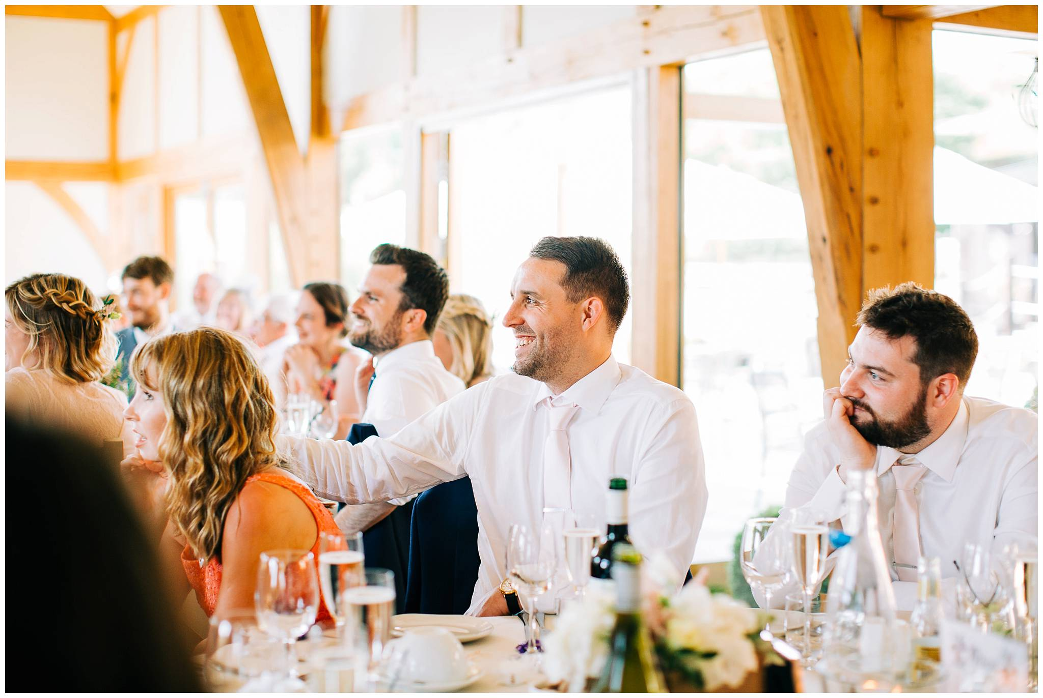 wedding guests at table laughing and smiling during speeches