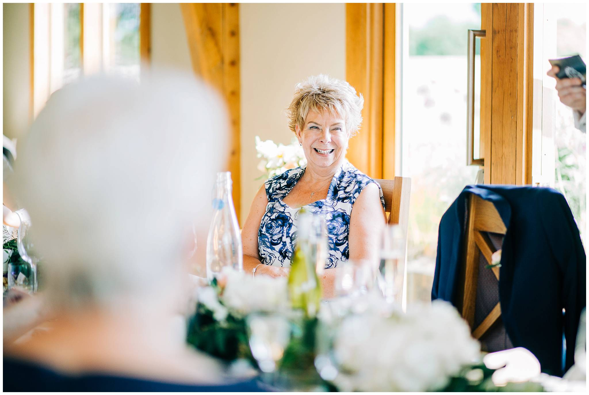 the mother of the groom is smiling as a reaction to the grooms speech