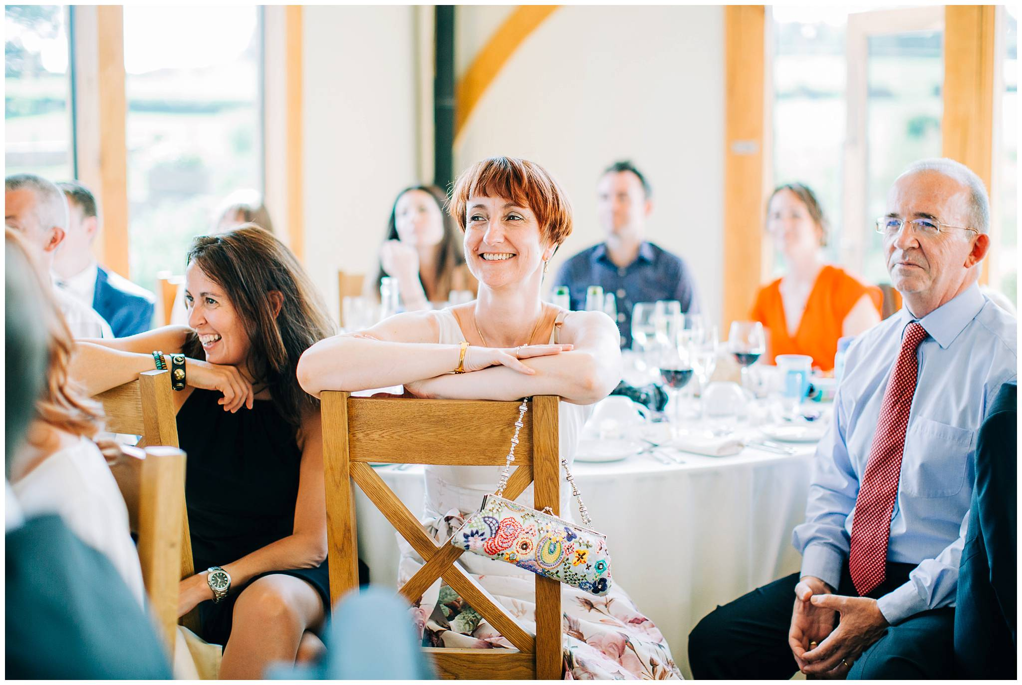 a guest is resting her arms on the back of her chair and is enjoying the speeches