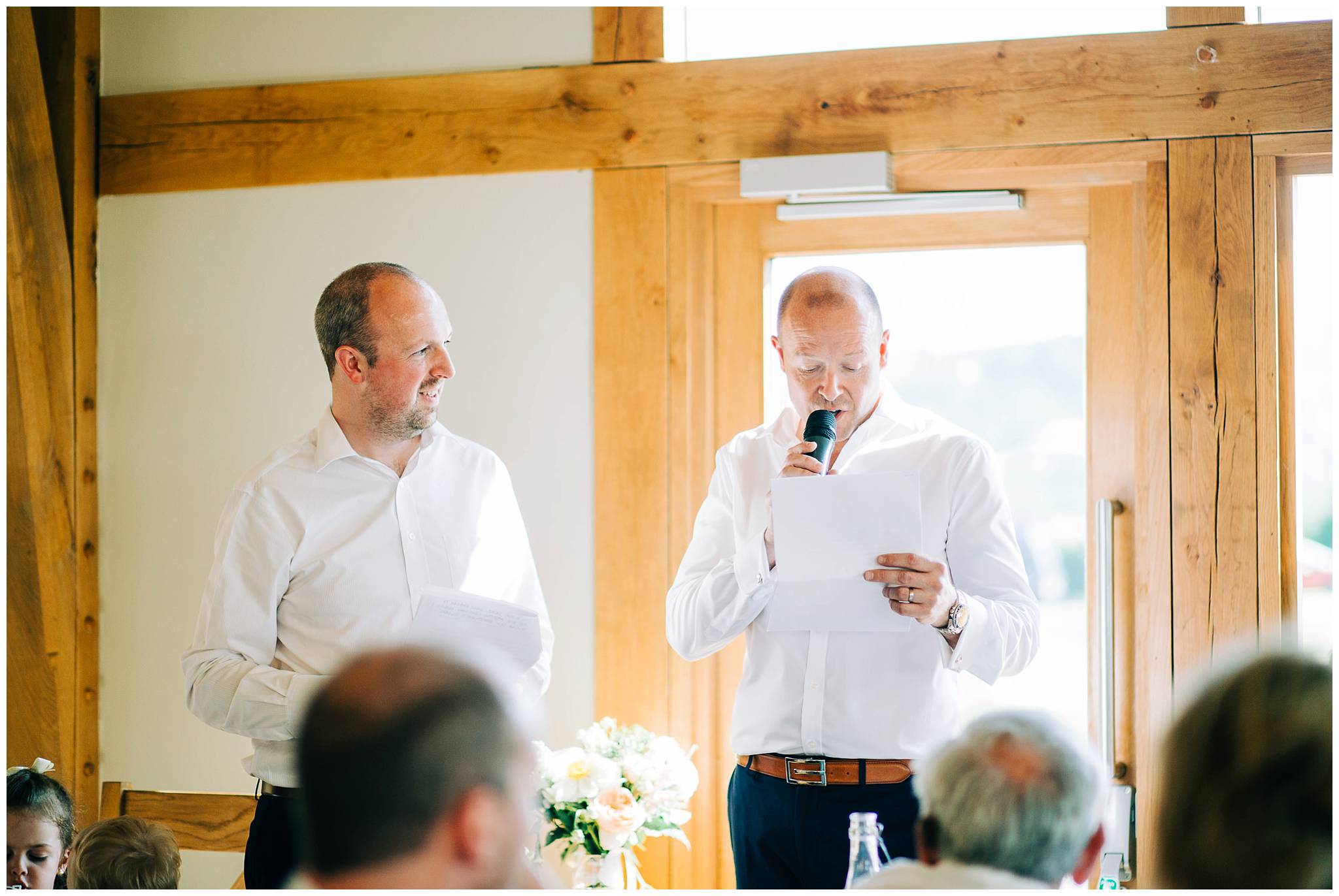 the two best men are stood up with the microphone giving their joint best man speech