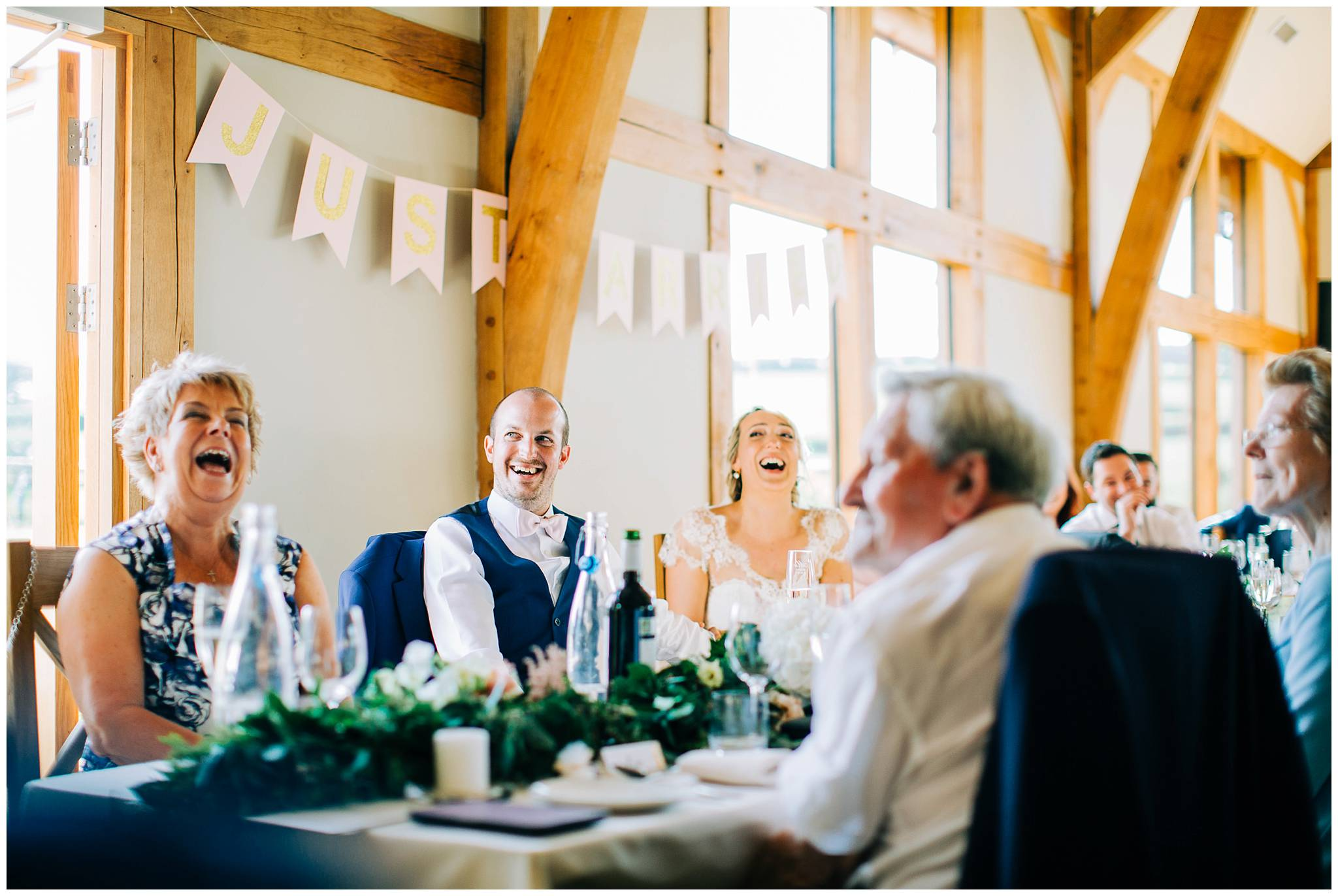 everyone is in hysterical laughter on the top table during the best man speech