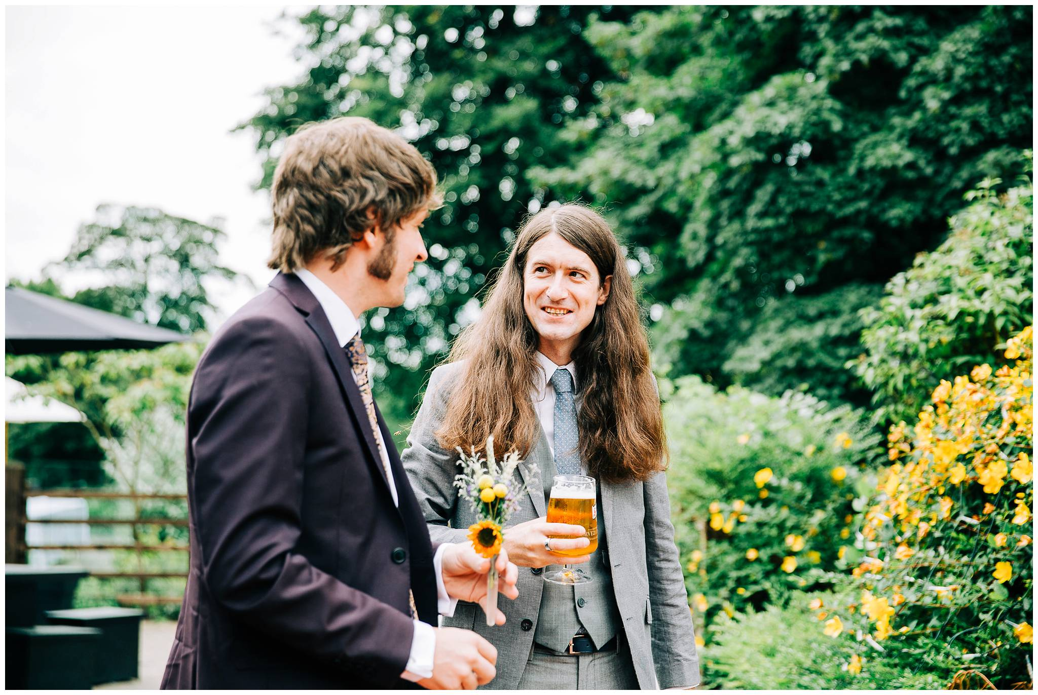 groom talking to smiling guests with long hair holding a beer