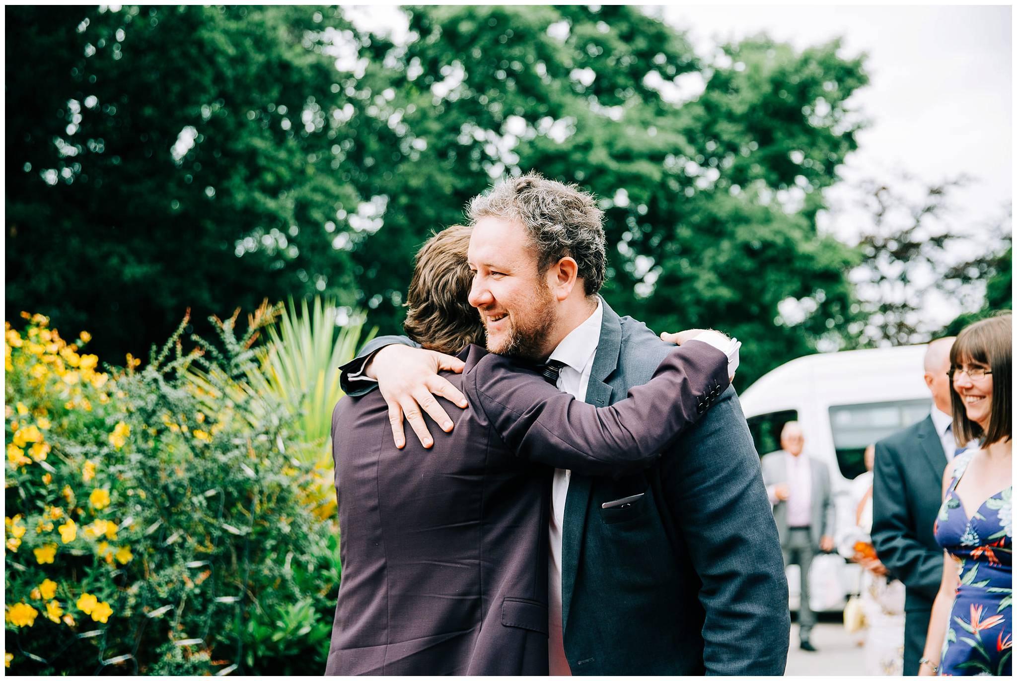 groom hugging an arriving wedding guest
