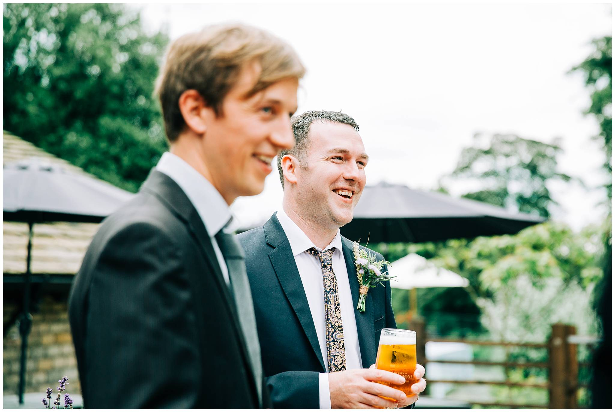 two male wedding guests smiling and holding beers