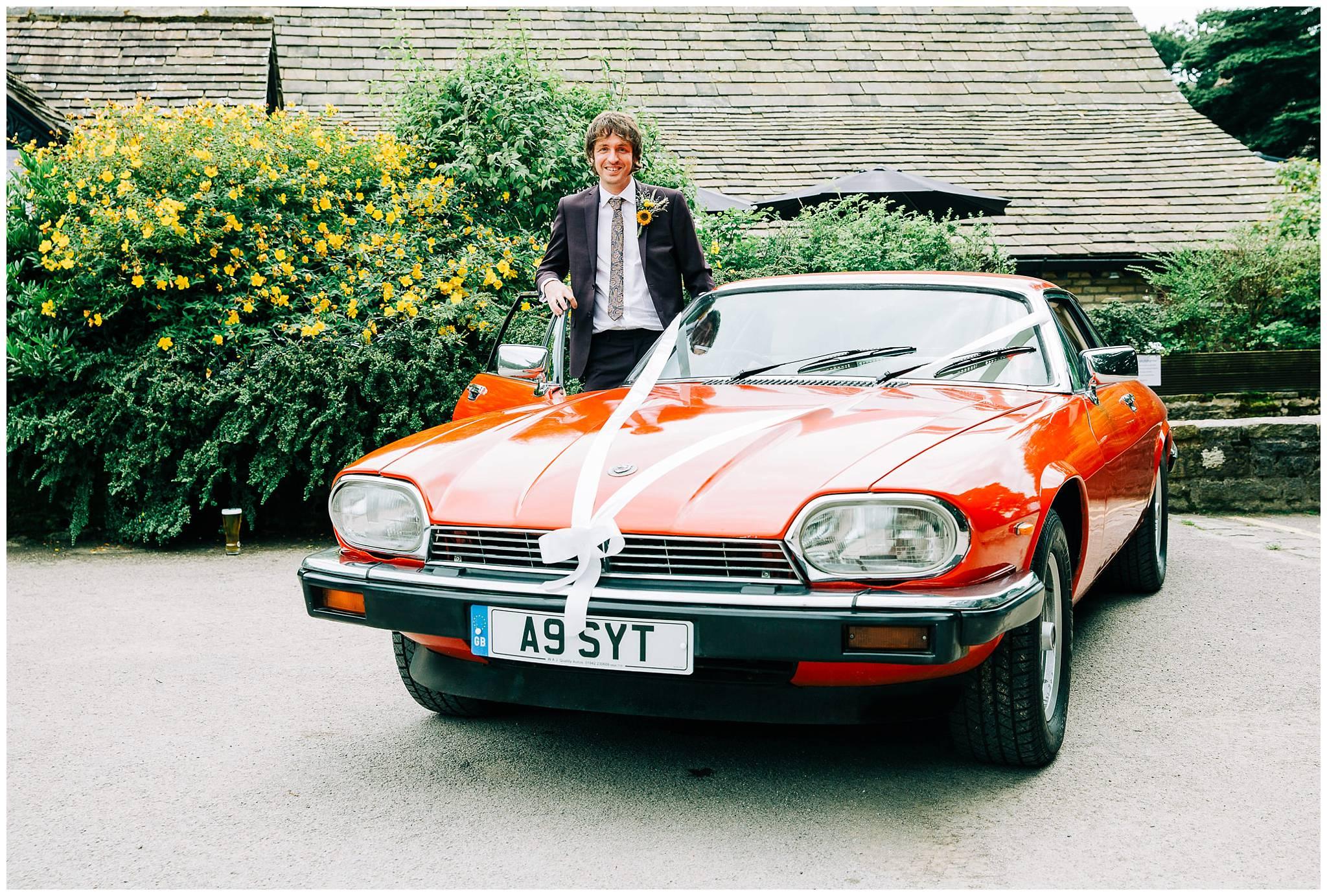groom stood in open car door of red vintage car