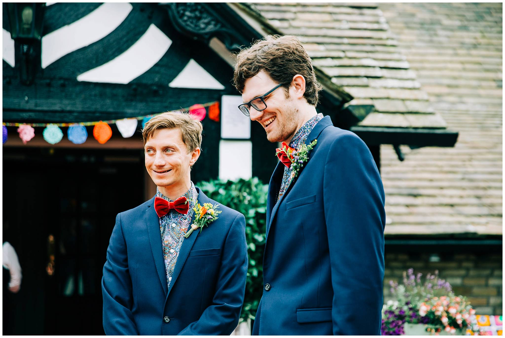 two men dressed in colourful paisley shirts and red velvet bow ties