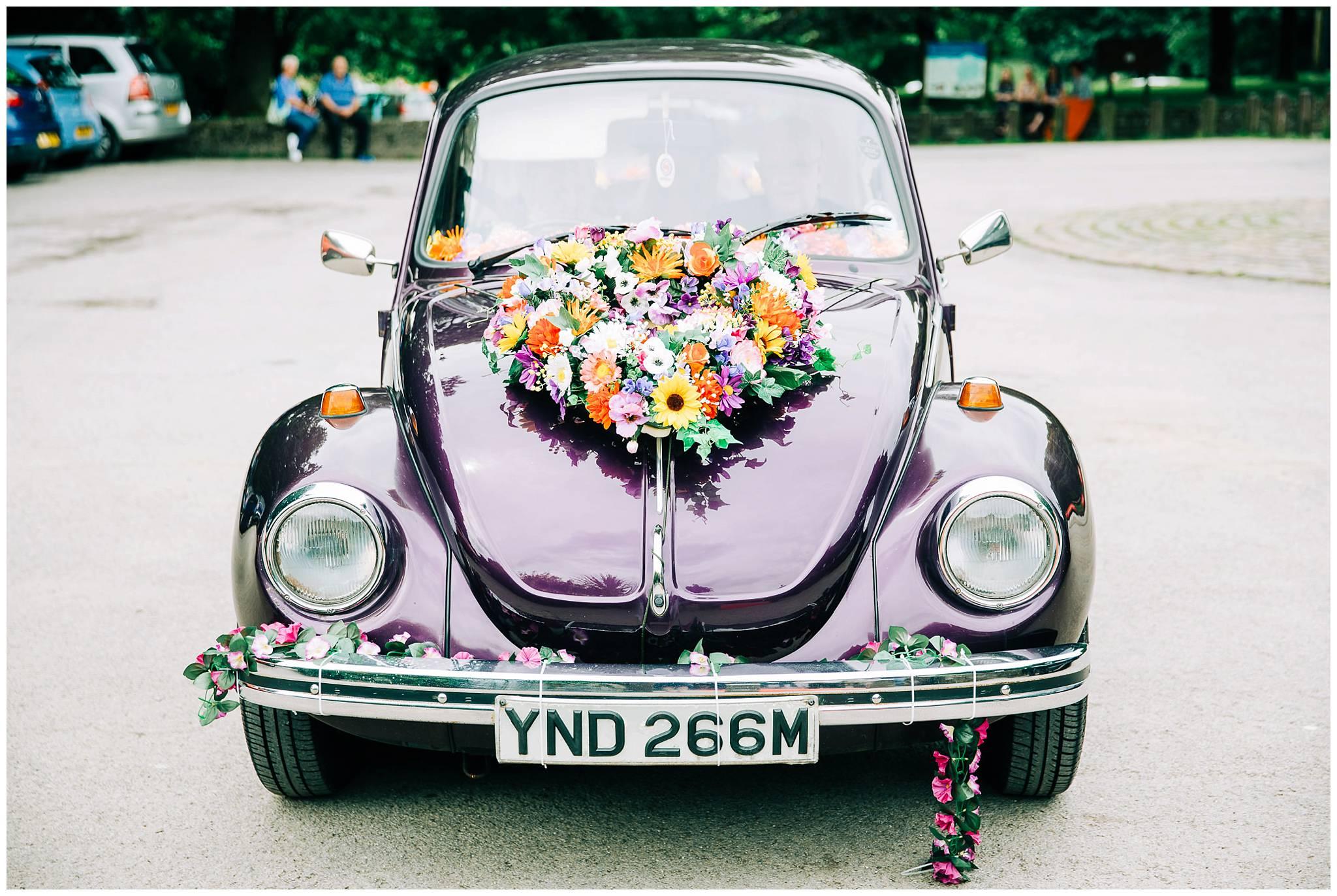 vintage purple VW beetle with floral heart shaped arrangemen on front