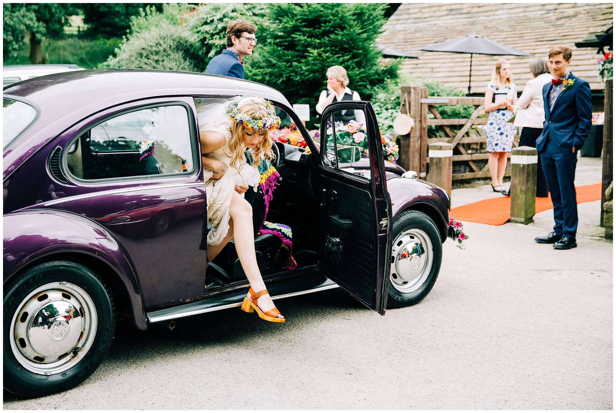bride steps out of vintage purple VW beetle