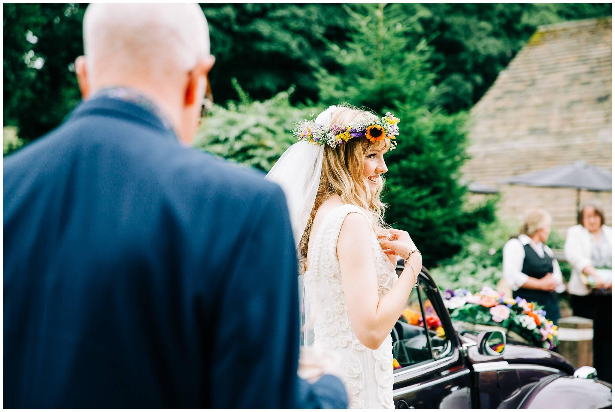 smiling bride adjusting her wedding dress staps
