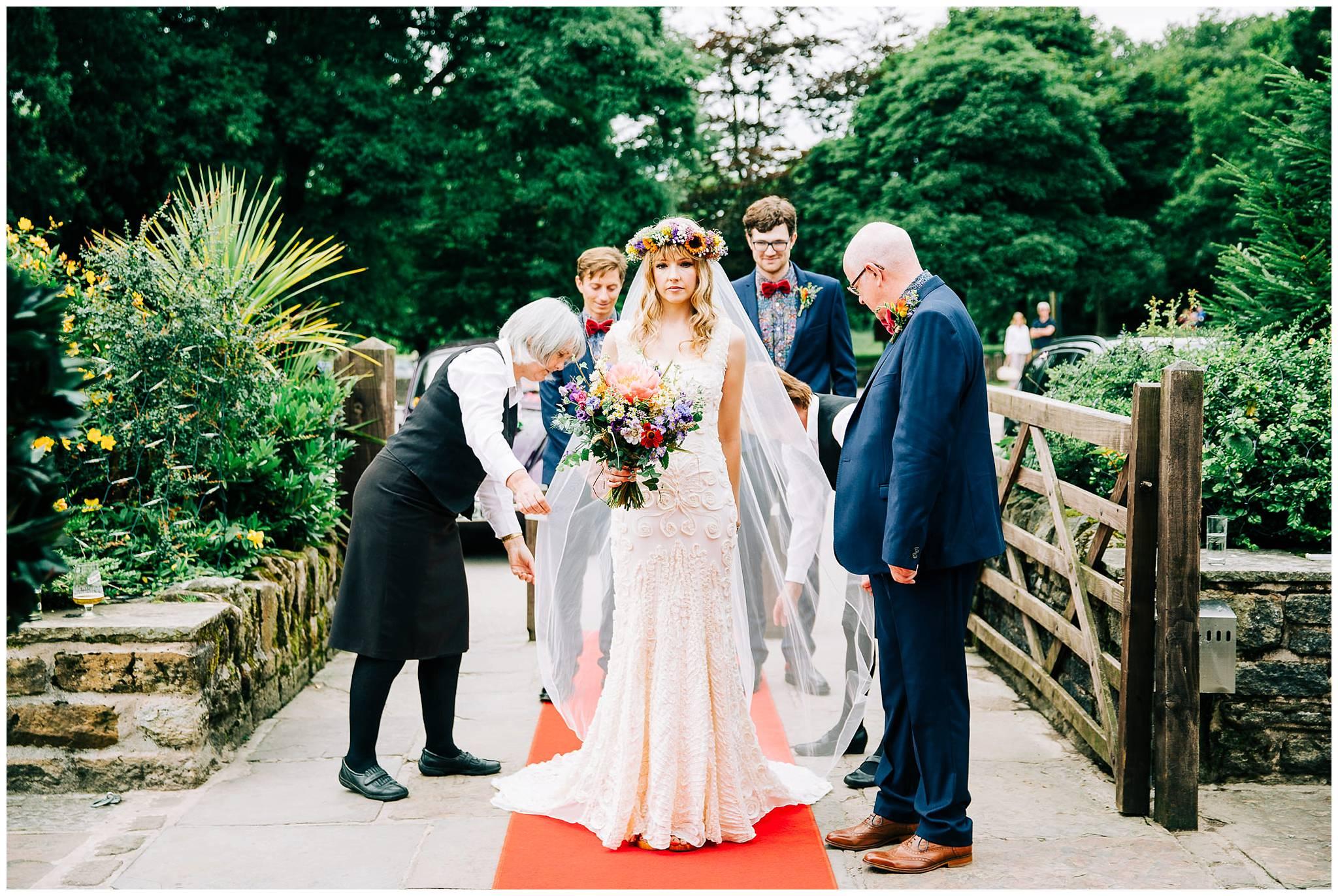bride ooking nervous on red carpet whilst having veil arranged