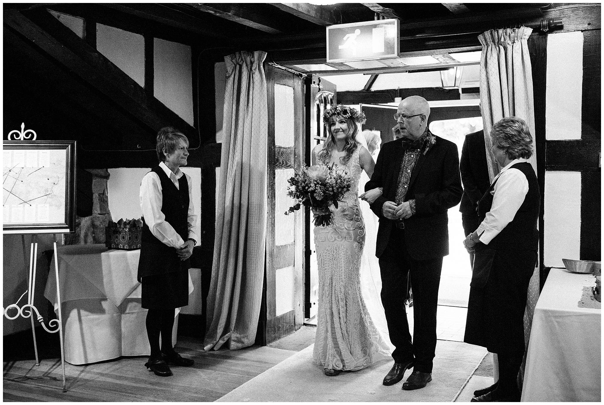 bride enters linking father with large smile on her face