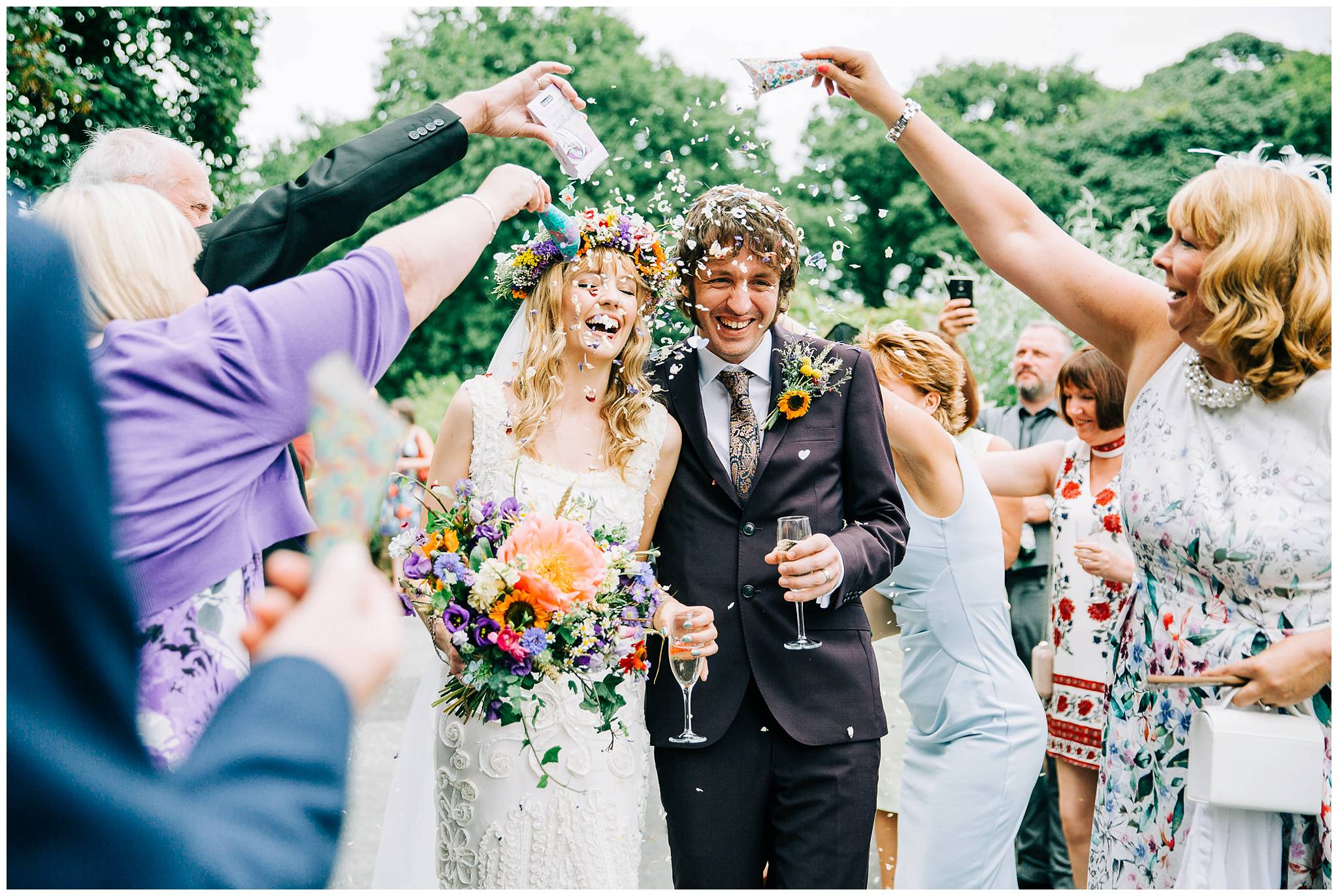bride and groom laughing hysterically whilst getting mouth full of confetti