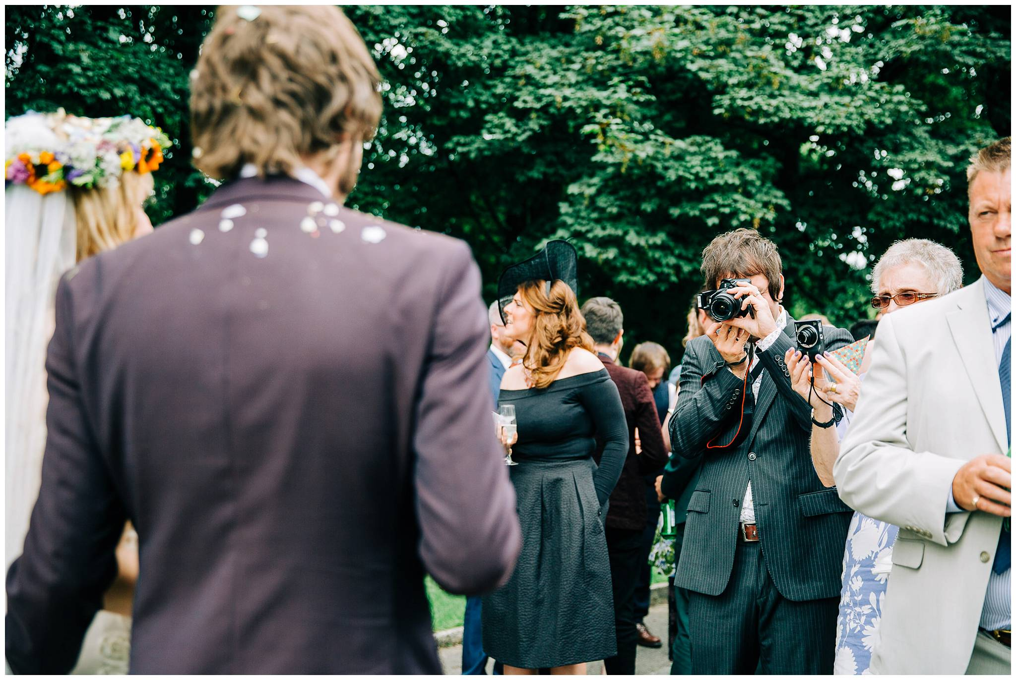 guest with camera talking photo of bride and groom