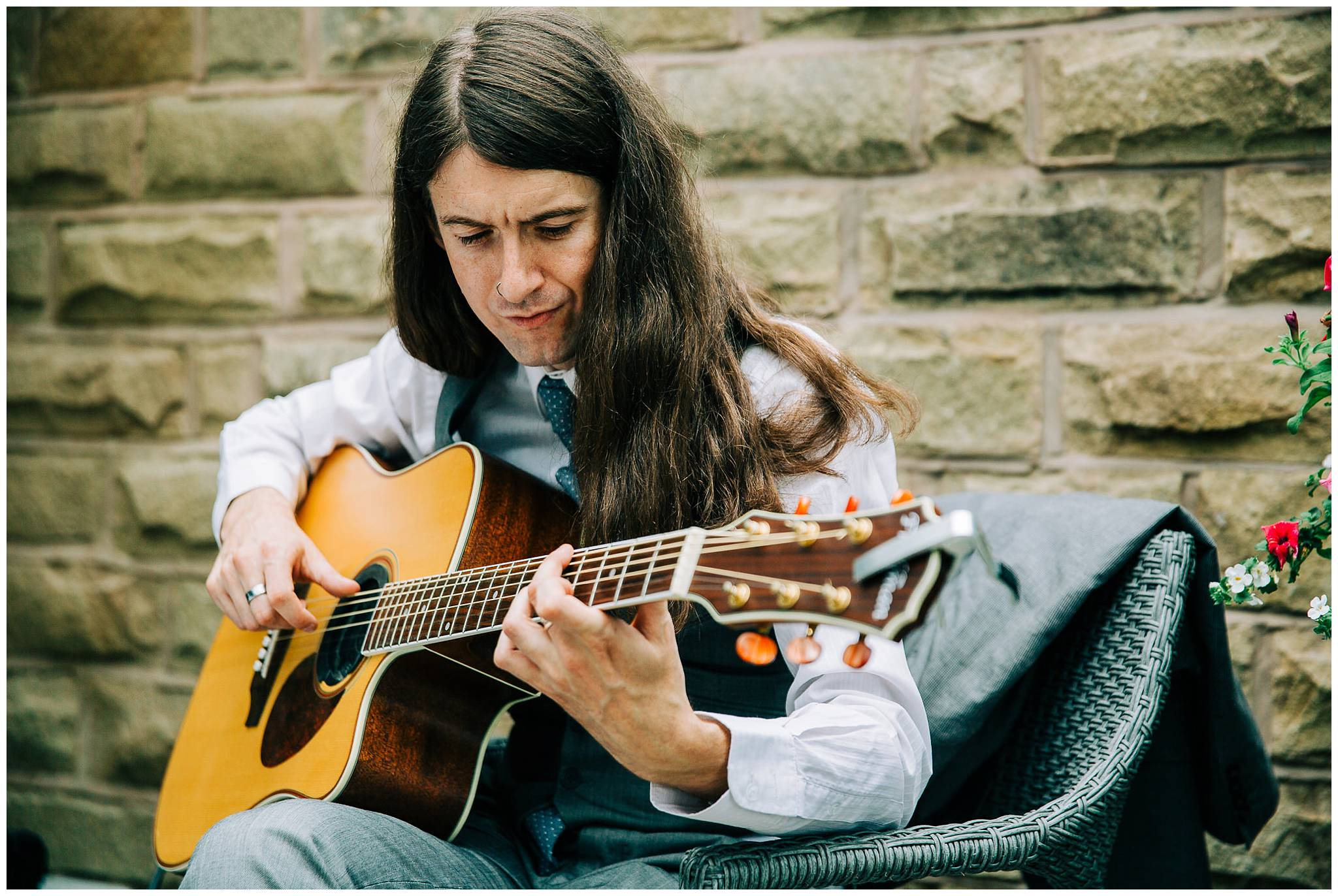 long haired man playing acoustic guitar