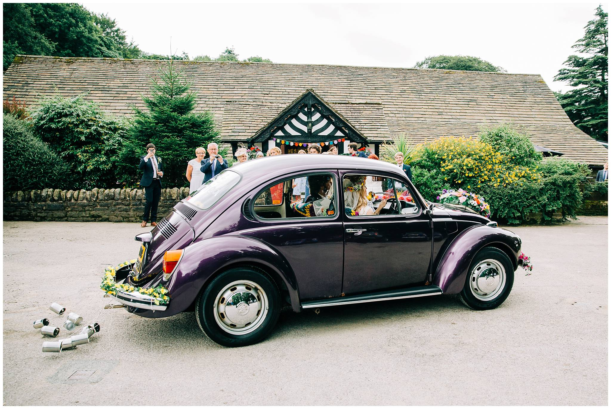 bride driving vintage VW beetle draggin tin cans behind