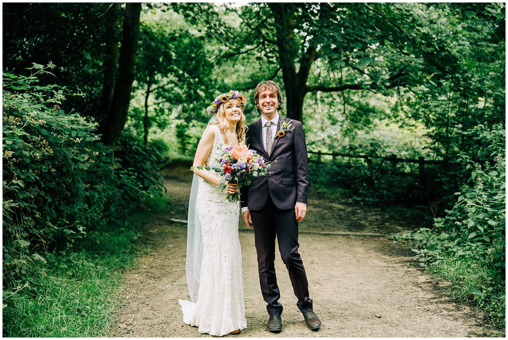 bride and groom stood in woodland setting smiling