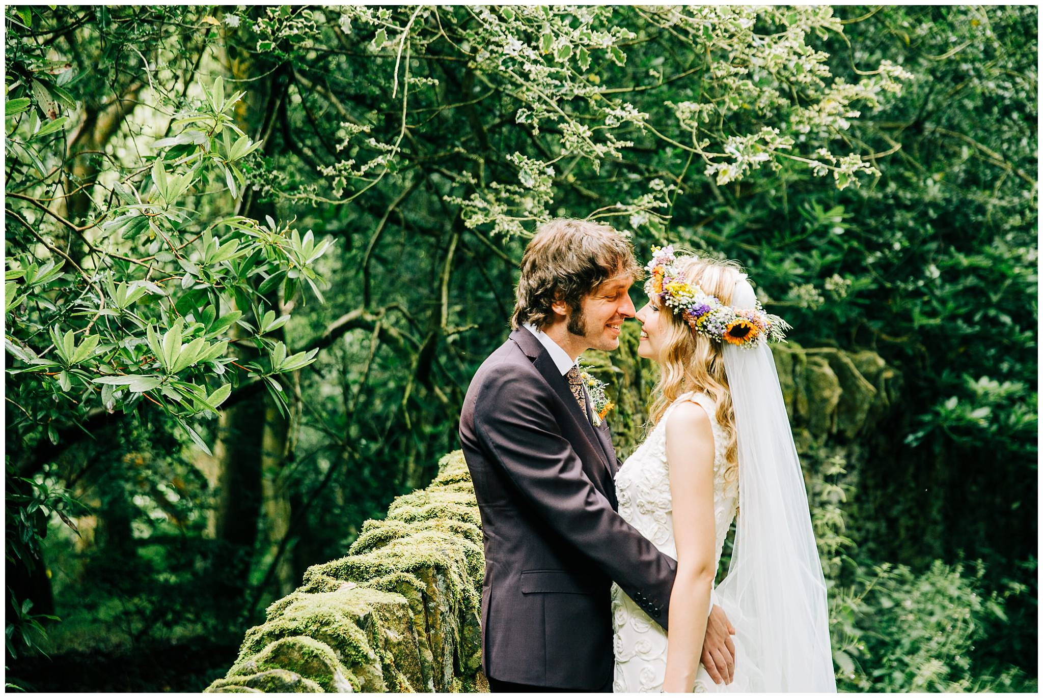 groom leaning against stone wall with his arms around bride