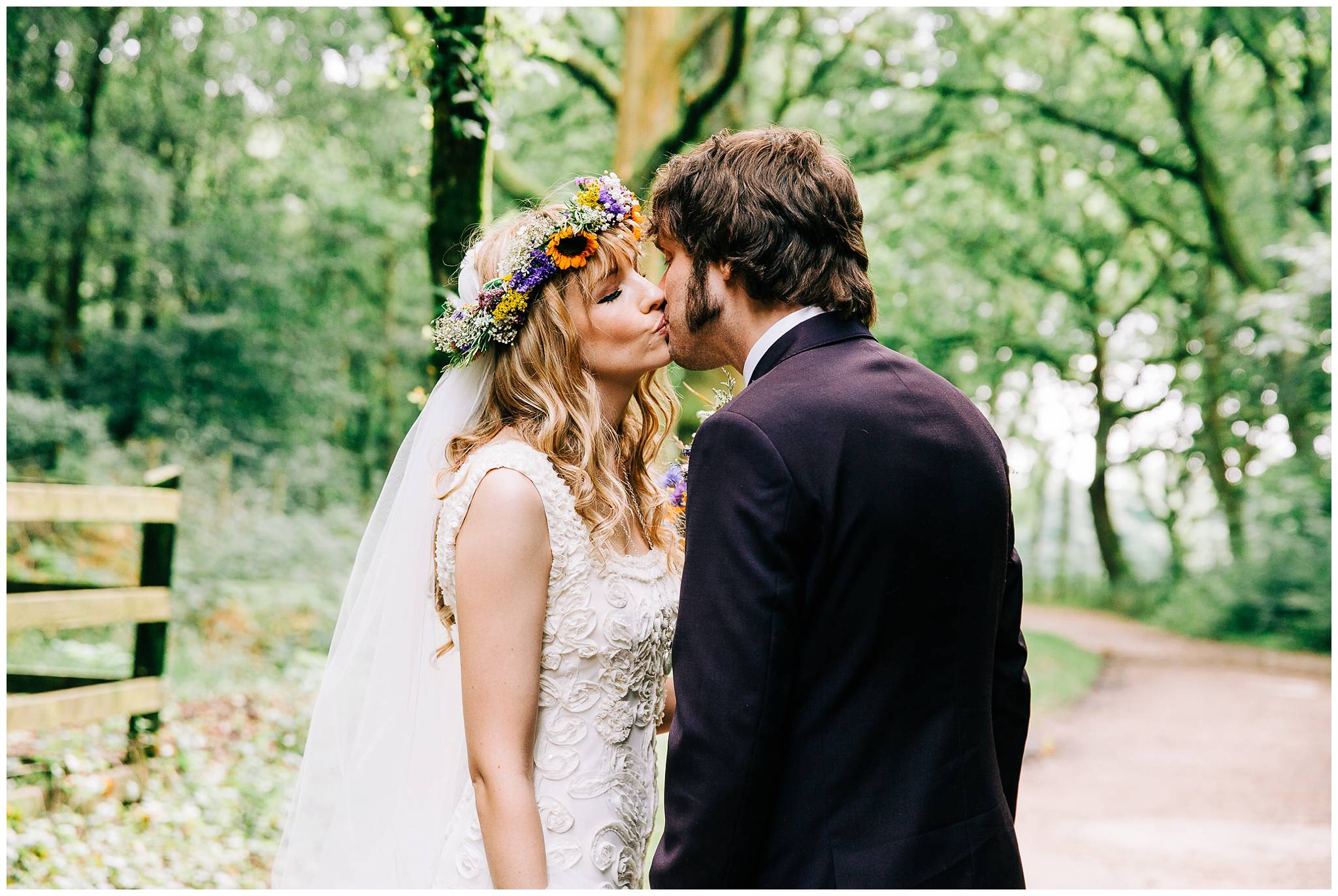 bride and groom kiss on tree lined path