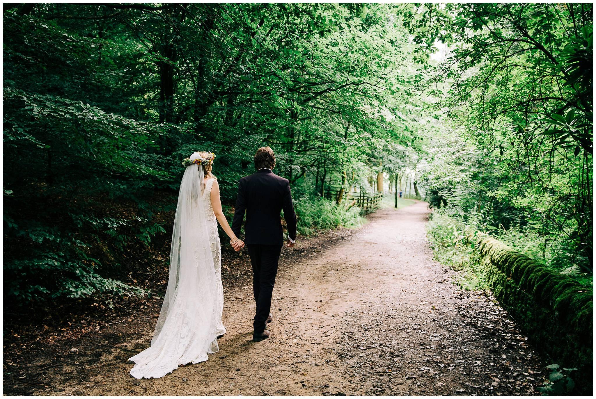 bride and groom walking away down woodland path