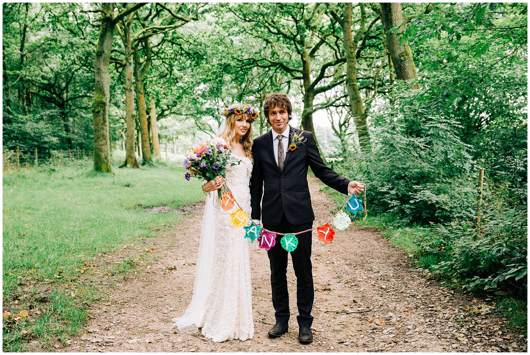 bride and groom hold up handmade crochet thank you bunting