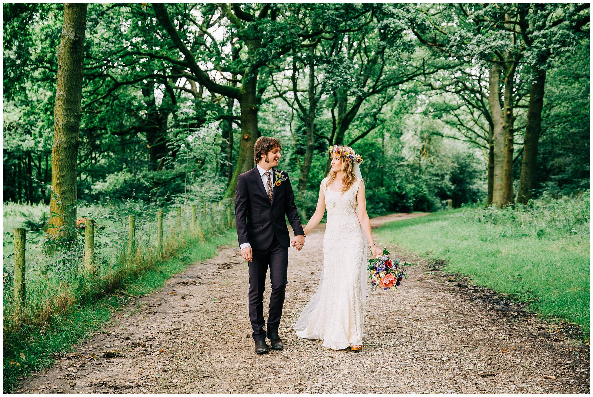 bride and groom walking and smiling at each other on woodland path