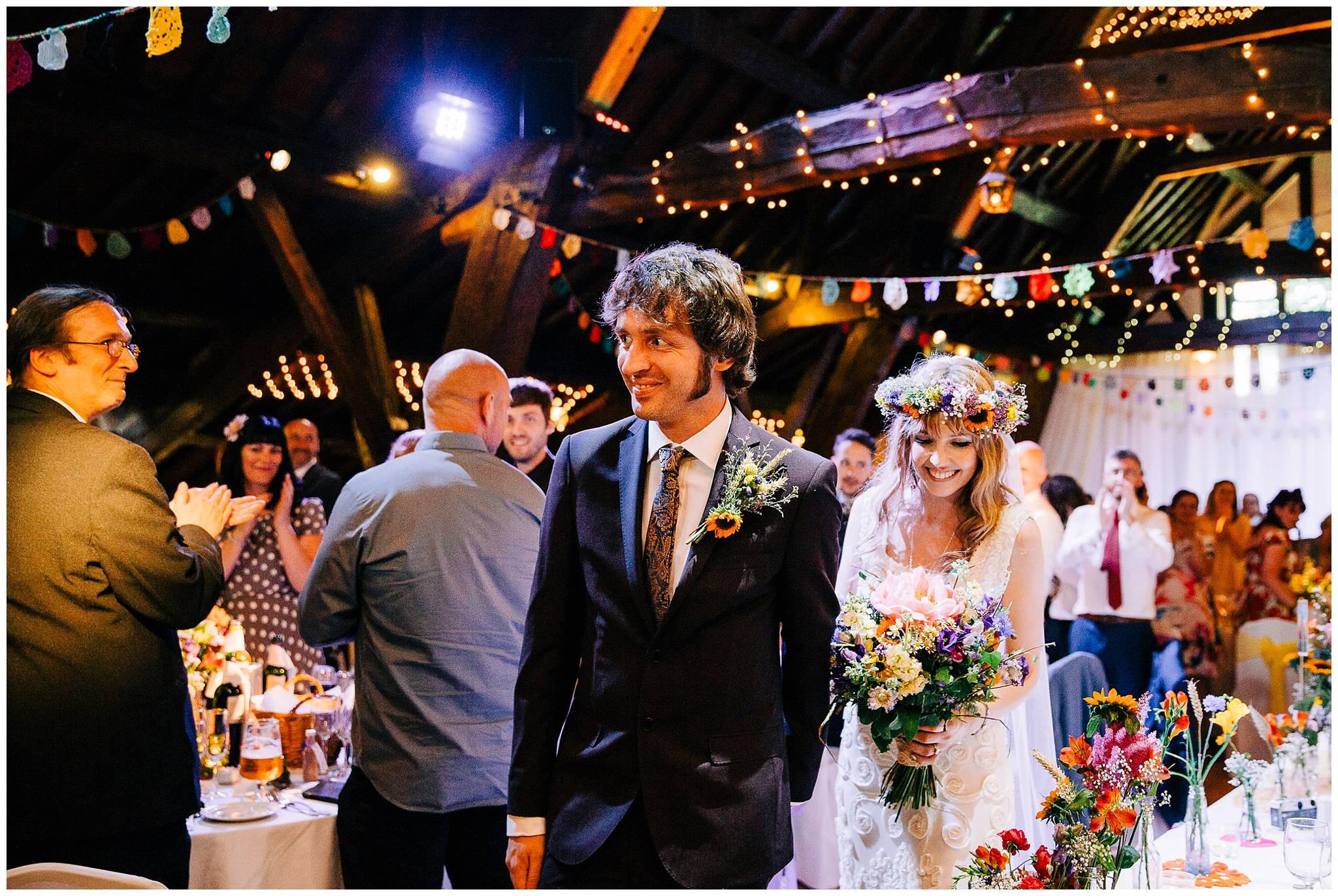 bride and groom enter wedding breakfast through guests