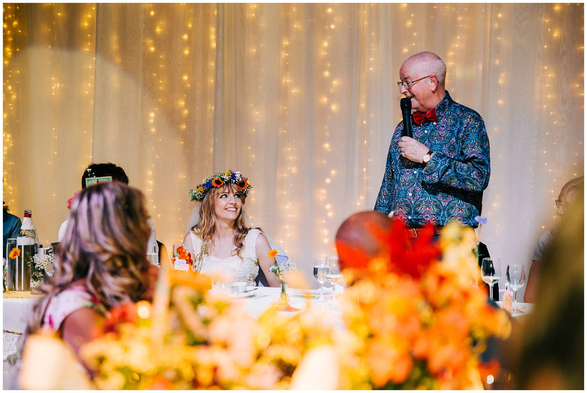 bride smiling and looking up at her father whilst he gives a speech