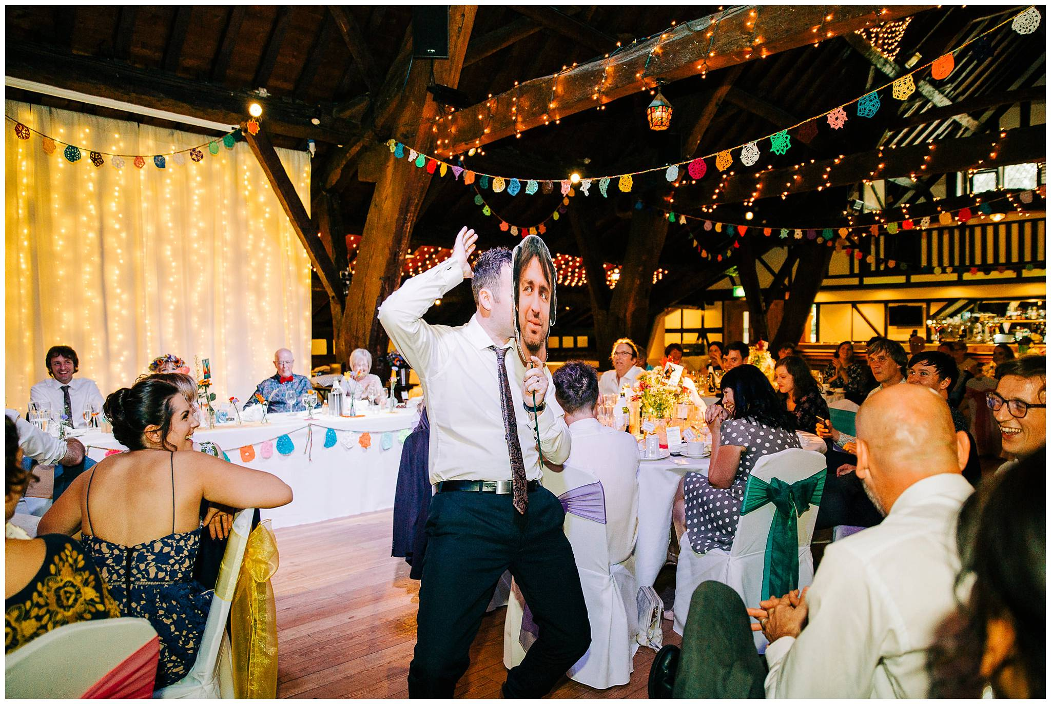 best man wearing cardboard grooms face whilst thrusting hips