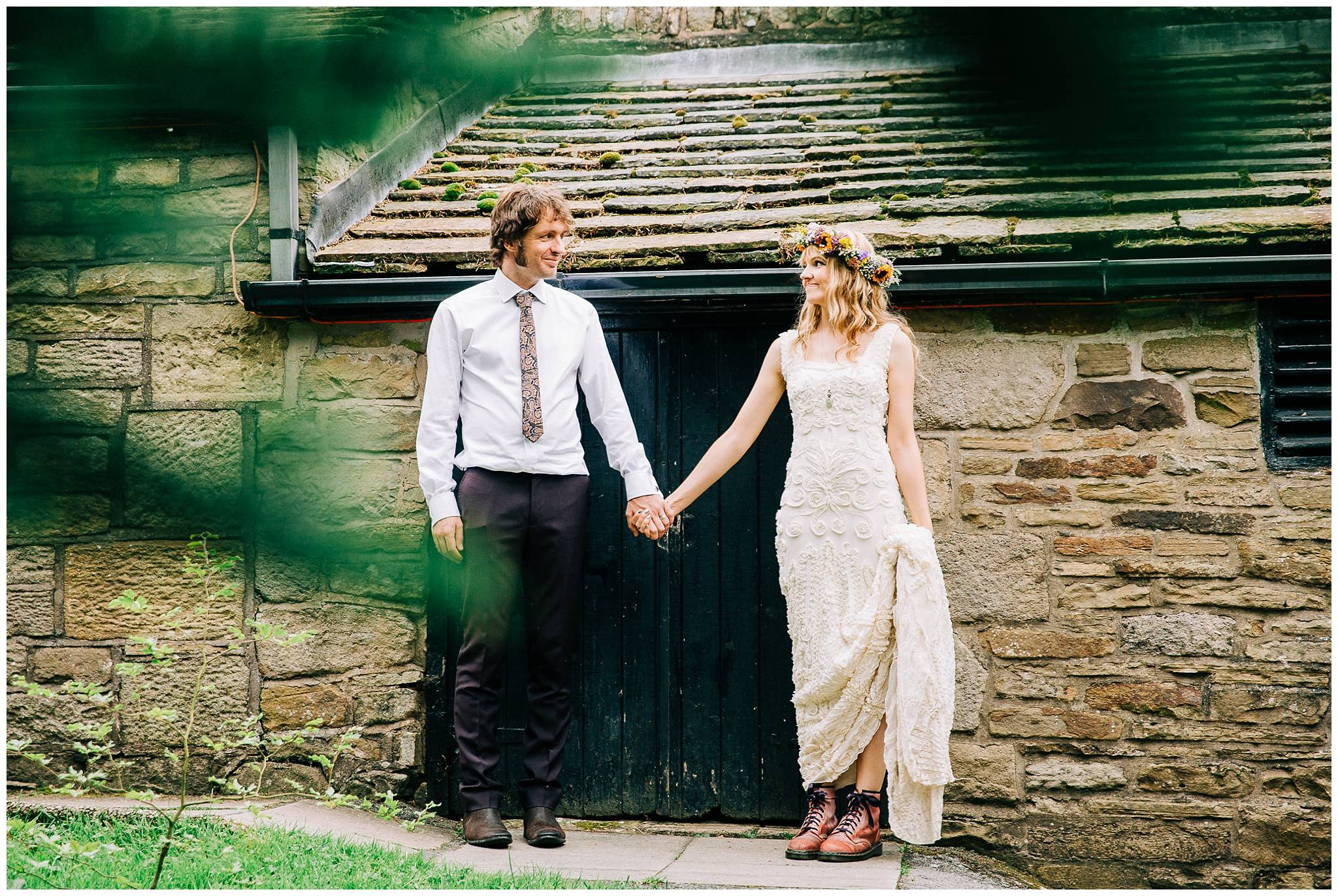 bride and groom stood infront of small black door holding hands and looking at each other