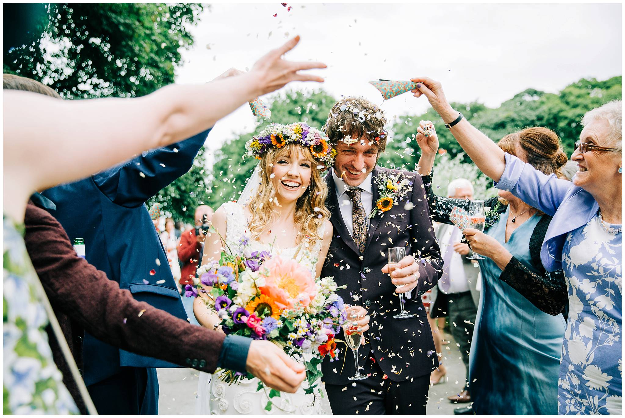 bride wearing floral crown walking with groom being showered in confetti
