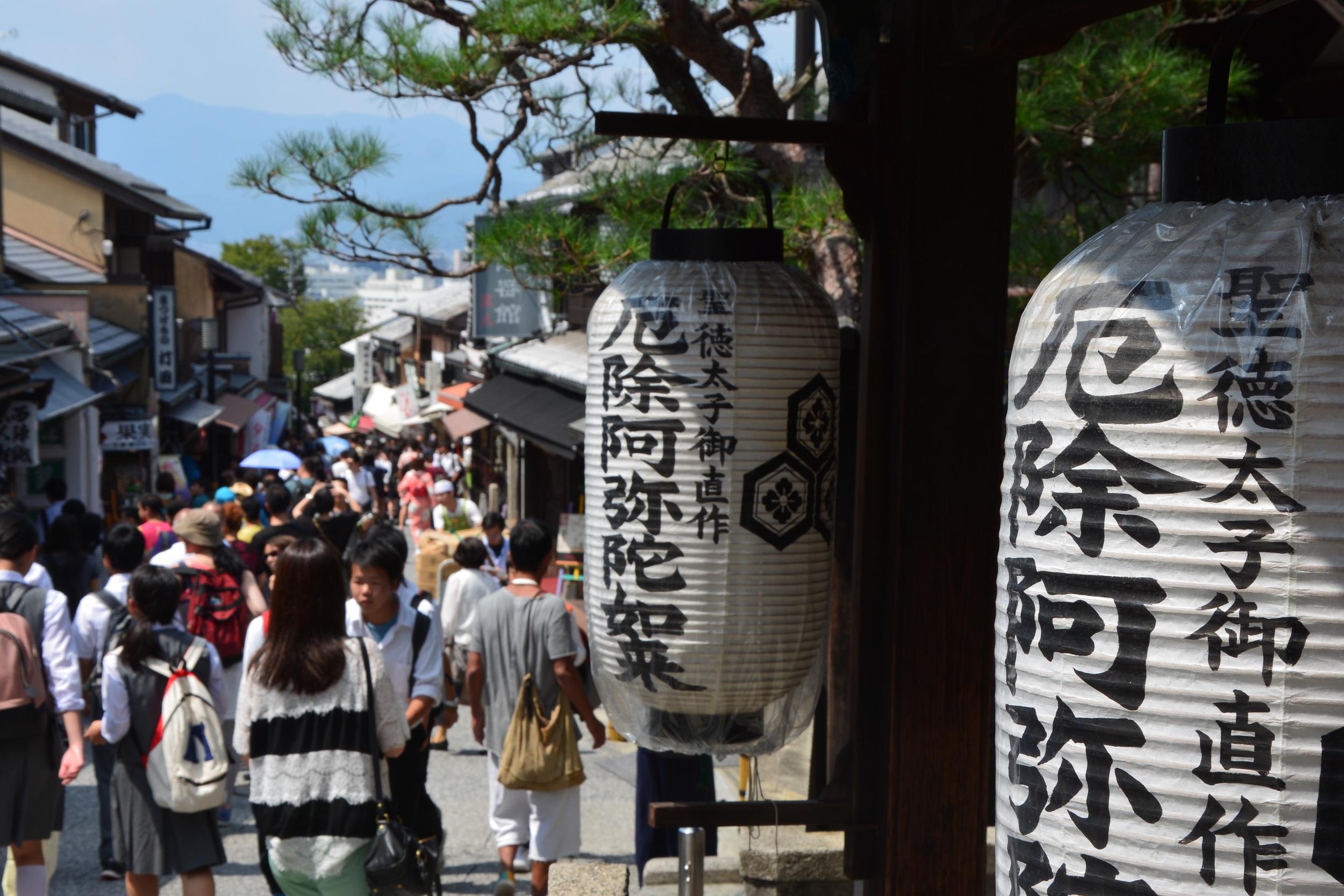 Crowded street scene - shops, food and tourists.