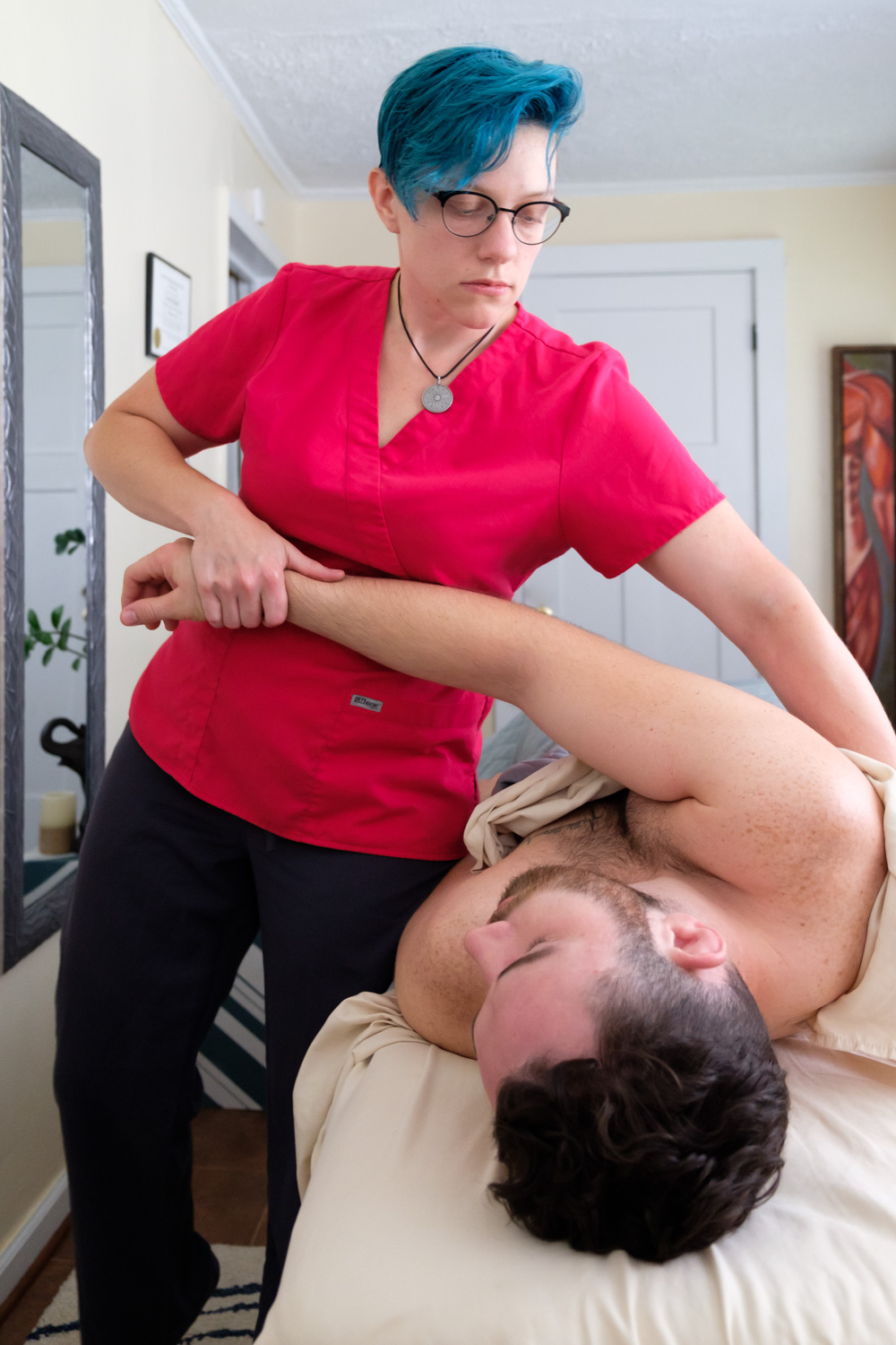 Massage therapist stretching client's arm.