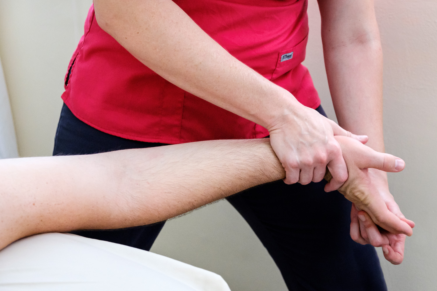 Female massage therapist stretching client's hand.