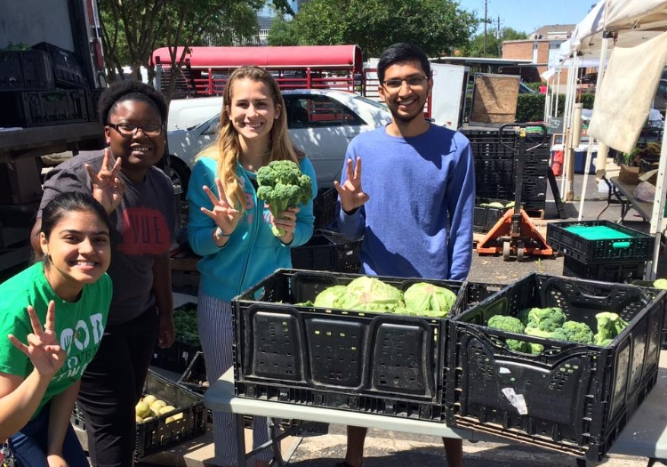 FRN at the University of Houston poses with recovered produce during a recovery at the Harvest Farmers Market.